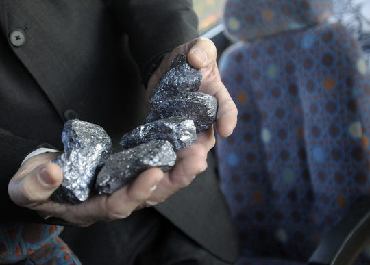 Randy George of the Montgomery Area Chamber of Commerce displays some of the high-grade silicon metal produced at Dow Corning as civic leaders take a bus tour of expanding businesses.