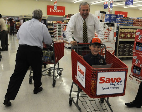 Montgomery Mayor Todd Strange pushes scout Jackson Cornelison, left, as they pass Montgomery Area Chamber President Randy George and scout Joseph Goodwin through the new grocery store on a scavenger hunt at the Save a Lot Food Store grand opening in 2010.