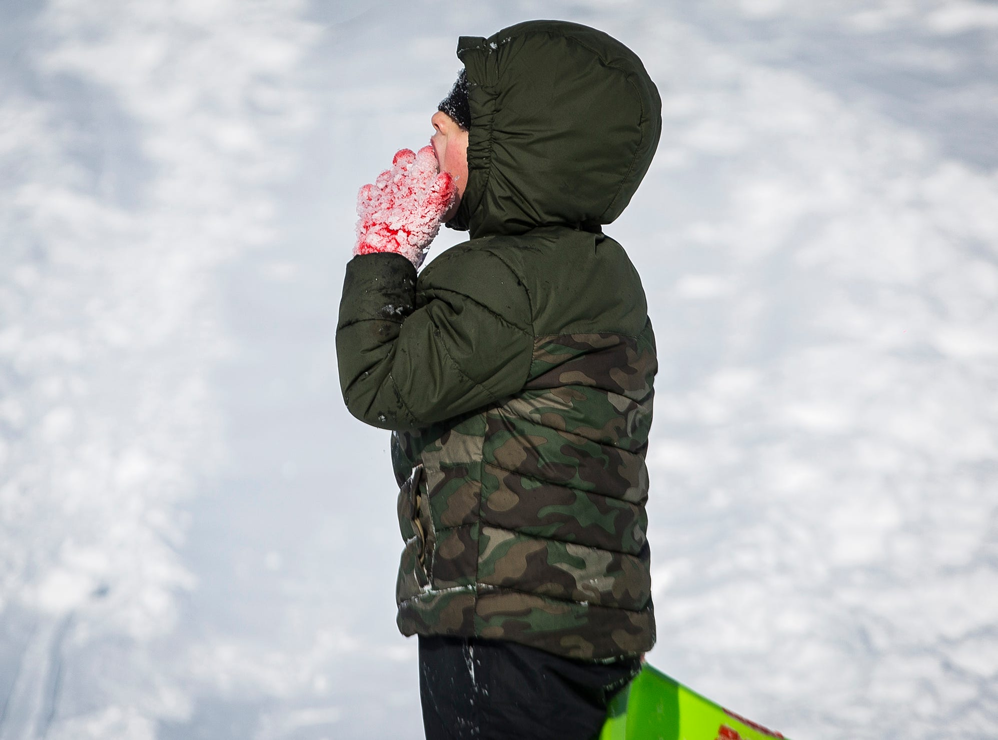 A child eats snow at McCulloch Park Friday afternoon.