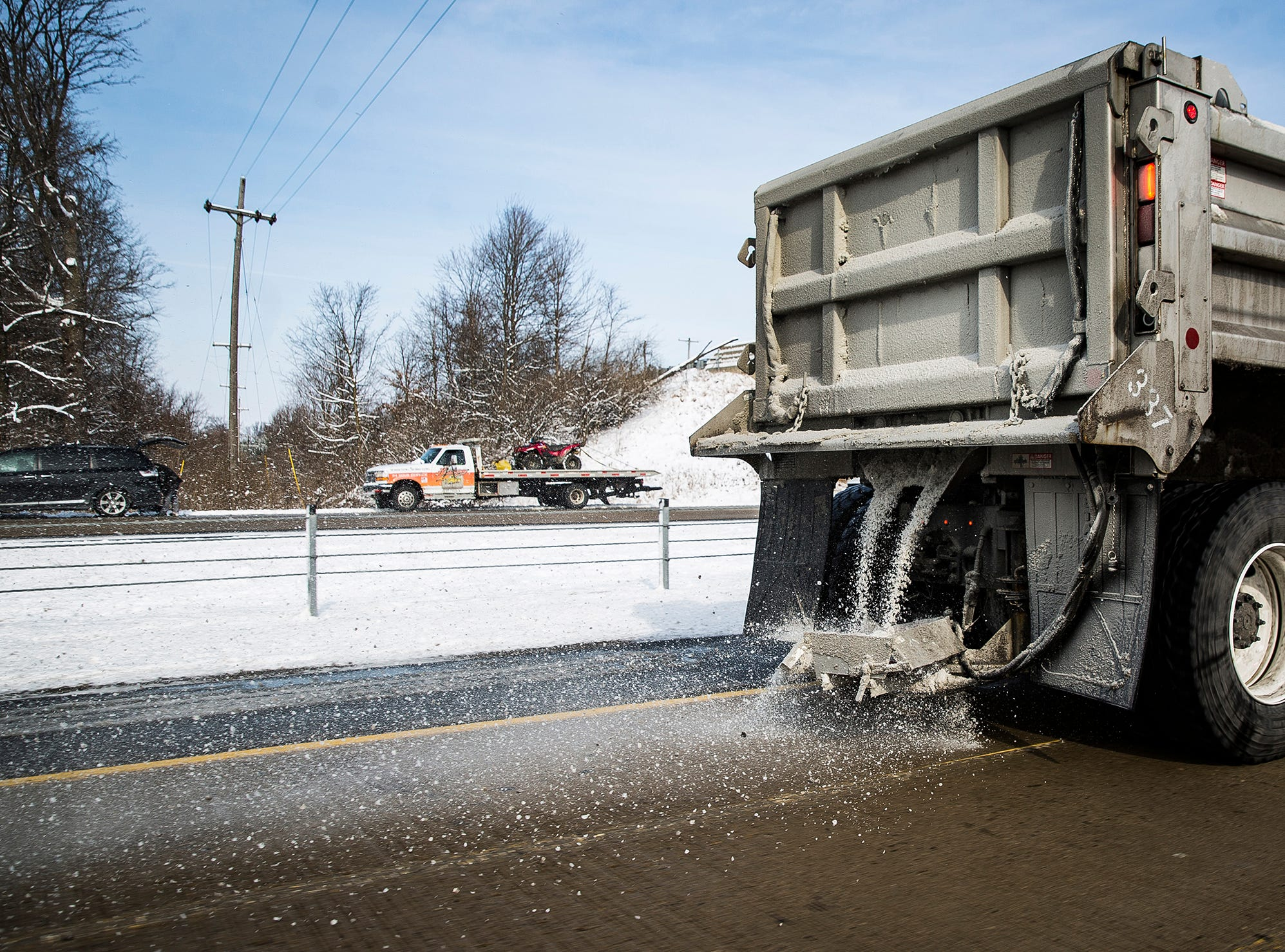 A salt truck drives along I-69 Friday afternoon.