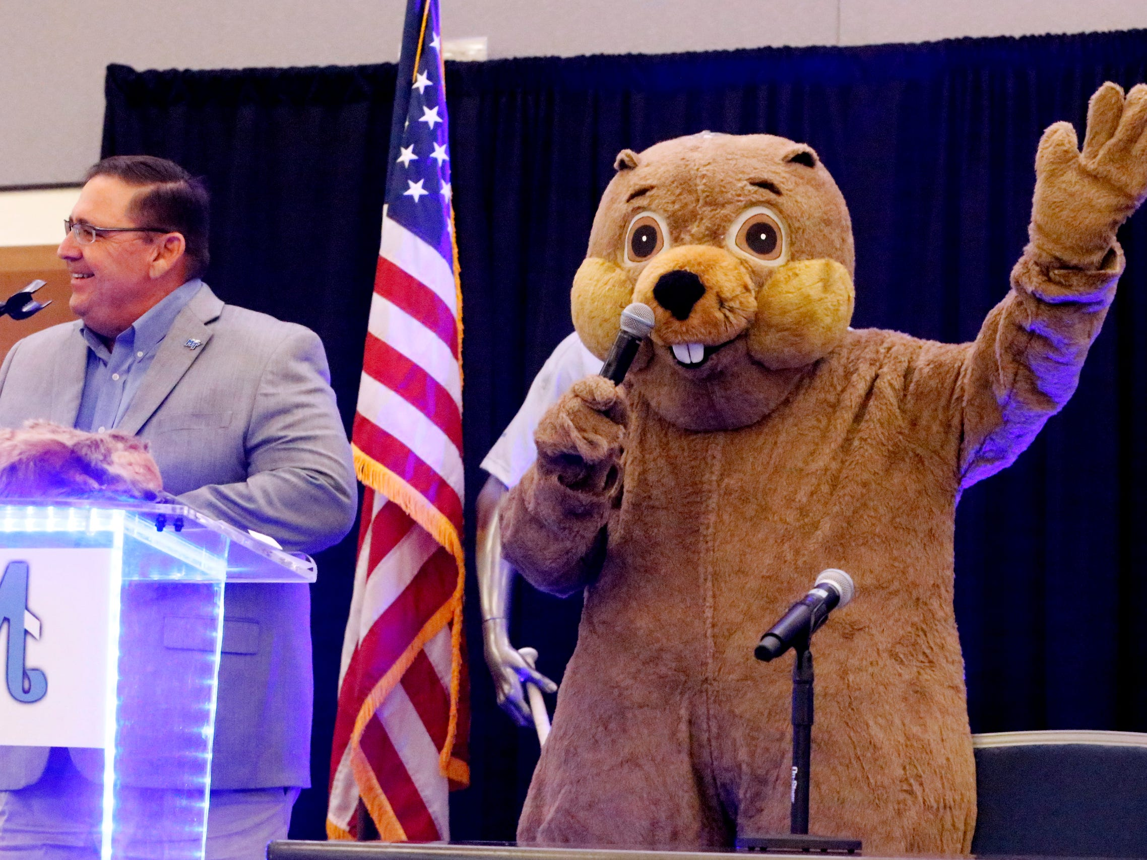 MTSU's new baseball coach Jim Toman, left, talks to the crowd on Friday, Feb. 1, 2019, as Raider 3 comes on stage at the annual MTSU baseball kickoff Groundhog Day Luncheon.