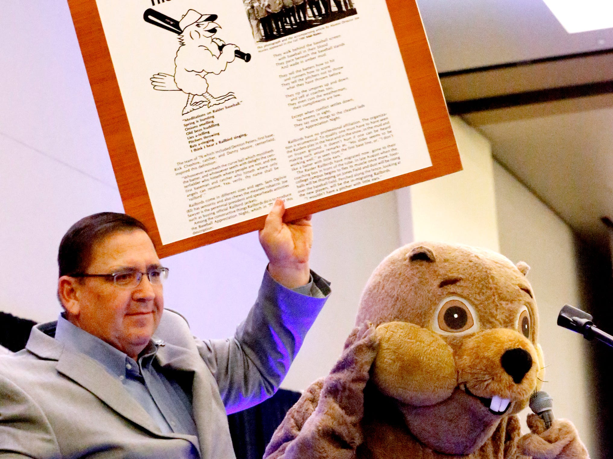 MTSU's new baseball coach Jim Toman holds up the history of the Railbirds on Friday, Feb. 1, 2019, as Raider 3 tells the history of the Groundhog Luncheon and the Railbirds during the MTSU baseball kickoff. It was revealed later that former MTSU baseball Coach Steve Peterson was in the Raider 3 costume.