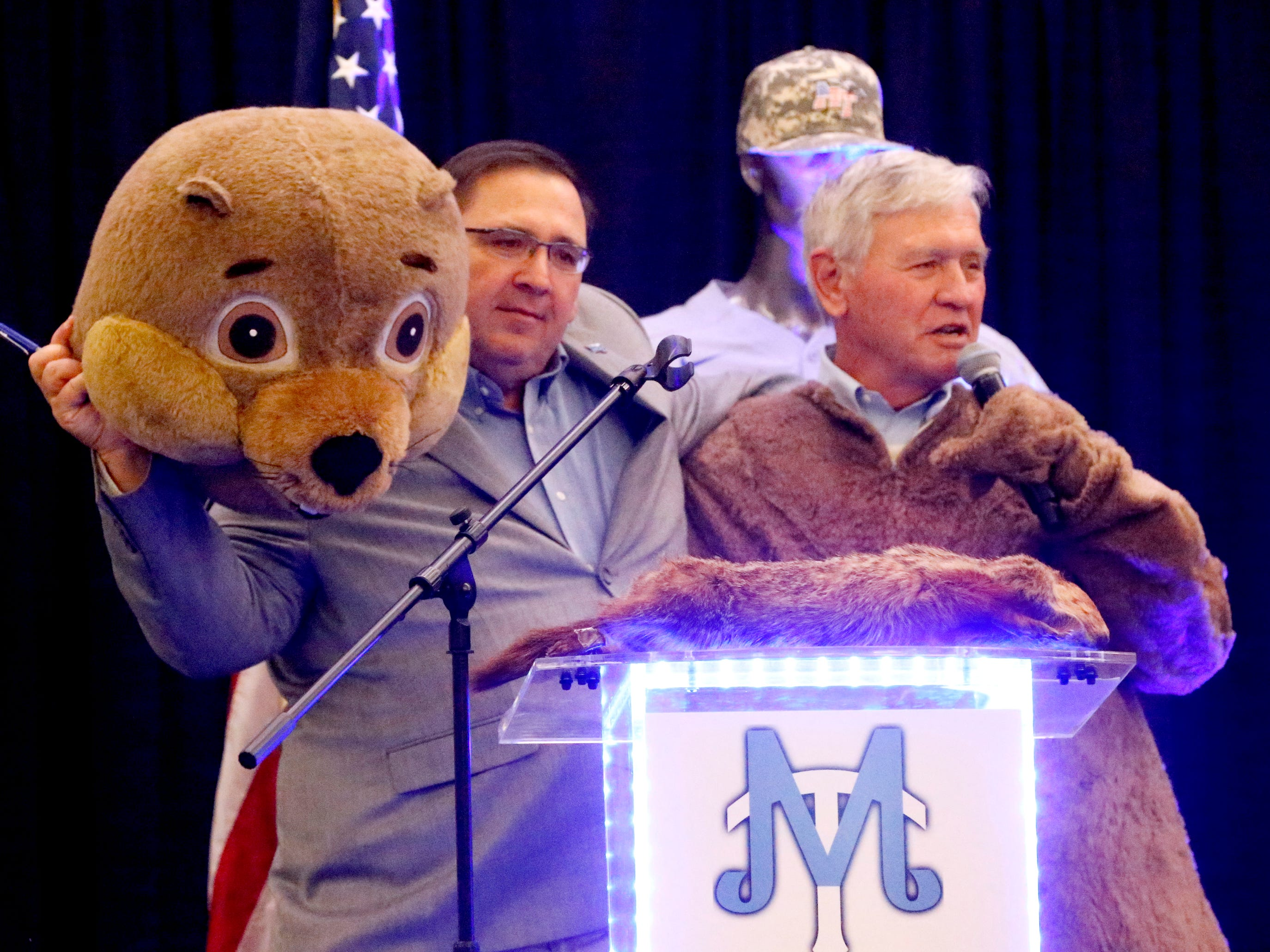 MTSU's new baseball coach Jim Toman, left, holds up the head of Raider 3 on Friday, Feb. 1, 2019, after it was revealed that former MTSU baseball Coach Steve Peterson was in the Raider 3 costume.
