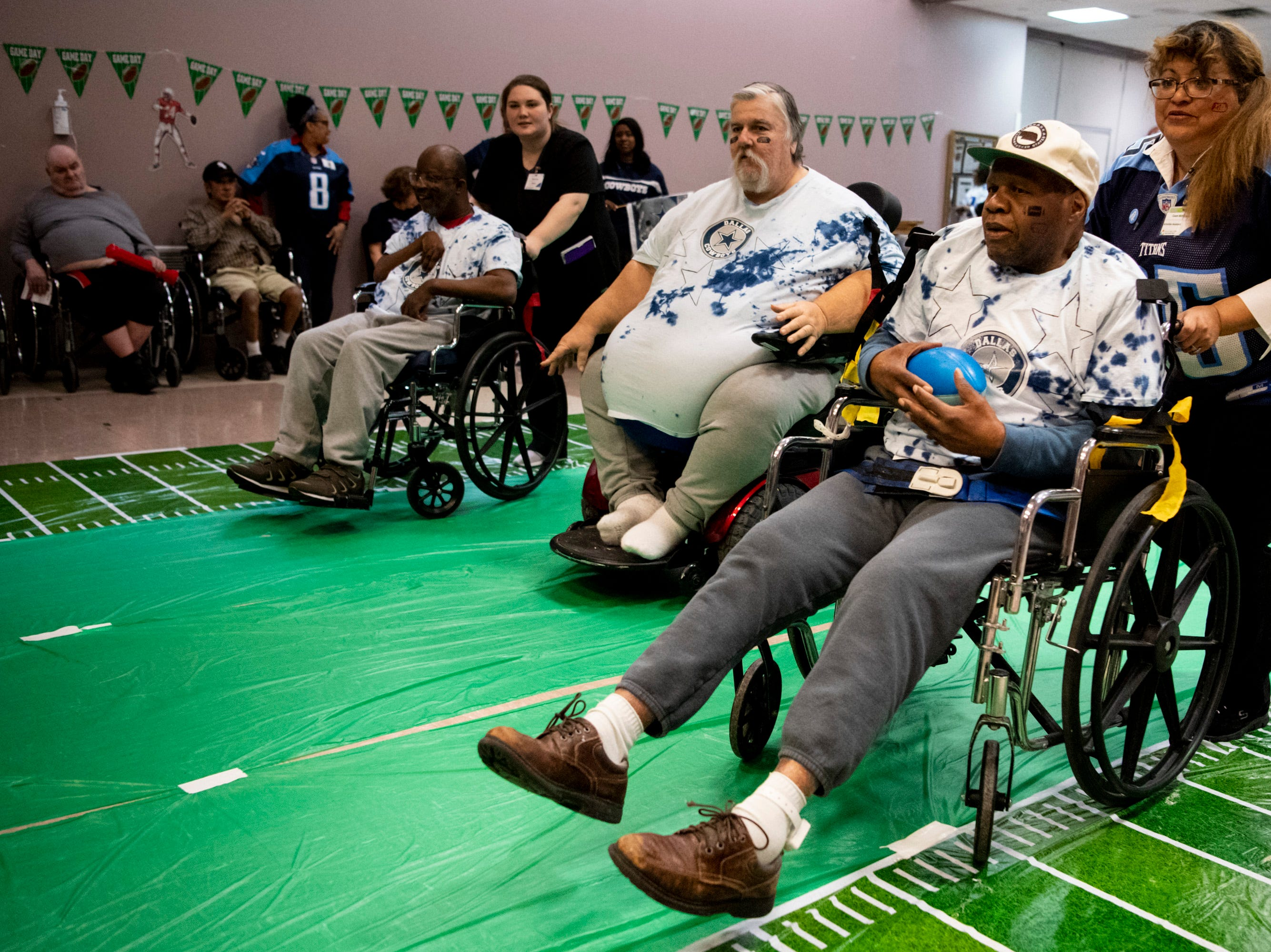 Nevel Blakemore advances with the ball with the aid of activities assistant Gwen McKissack during the Wheelchair Super Bowl at Nashville Community Care and Rehabilitation at Bordeaux in Nashville, Tenn., Friday, Feb. 1, 2019.