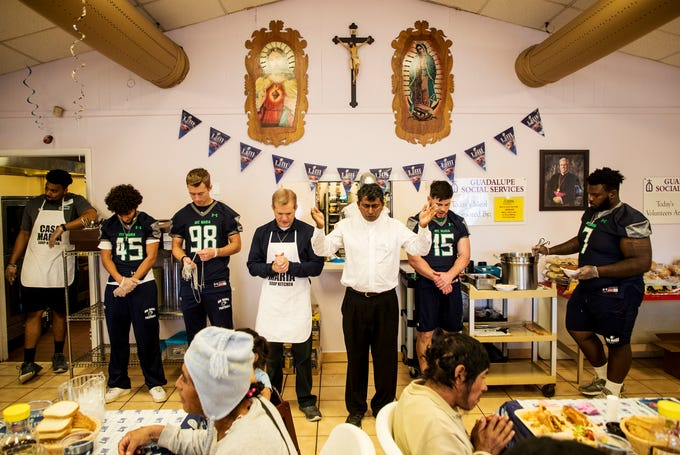 Father Ignatius Yeruva from Catholic Charities of prays over a super bowl tailgating meal at the Our Lady of Guadalupe Catholic Church in the Casa Maria Soup Kitchen in Immokalee on Friday 2/1/2019. Coaches and players from Ave Maria University football team cooked and served meals along with interacting with clients.