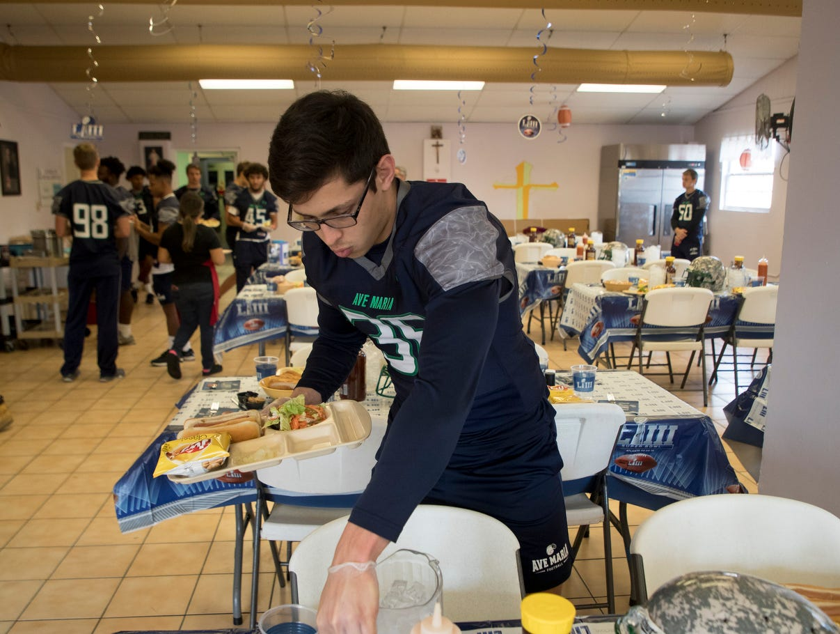 Ave Maria Unversity football player Alex Torres serves meals to clients at the third annual super bowl tailgating meal at the Our Lady of Guadalupe Catholic Church in the Casa Maria Soup Kitchen in Immokalee on Friday 2/1/2019. Coaches and players from Ave Maria University football team cooked and served meals along with interacting with clients.