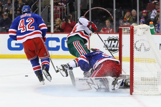 Jan 31, 2019; Newark, NJ, USA; New Jersey Devils left wing Miles Wood (44) collides with New York Rangers goaltender Henrik Lundqvist (30) during the second period at Prudential Center.