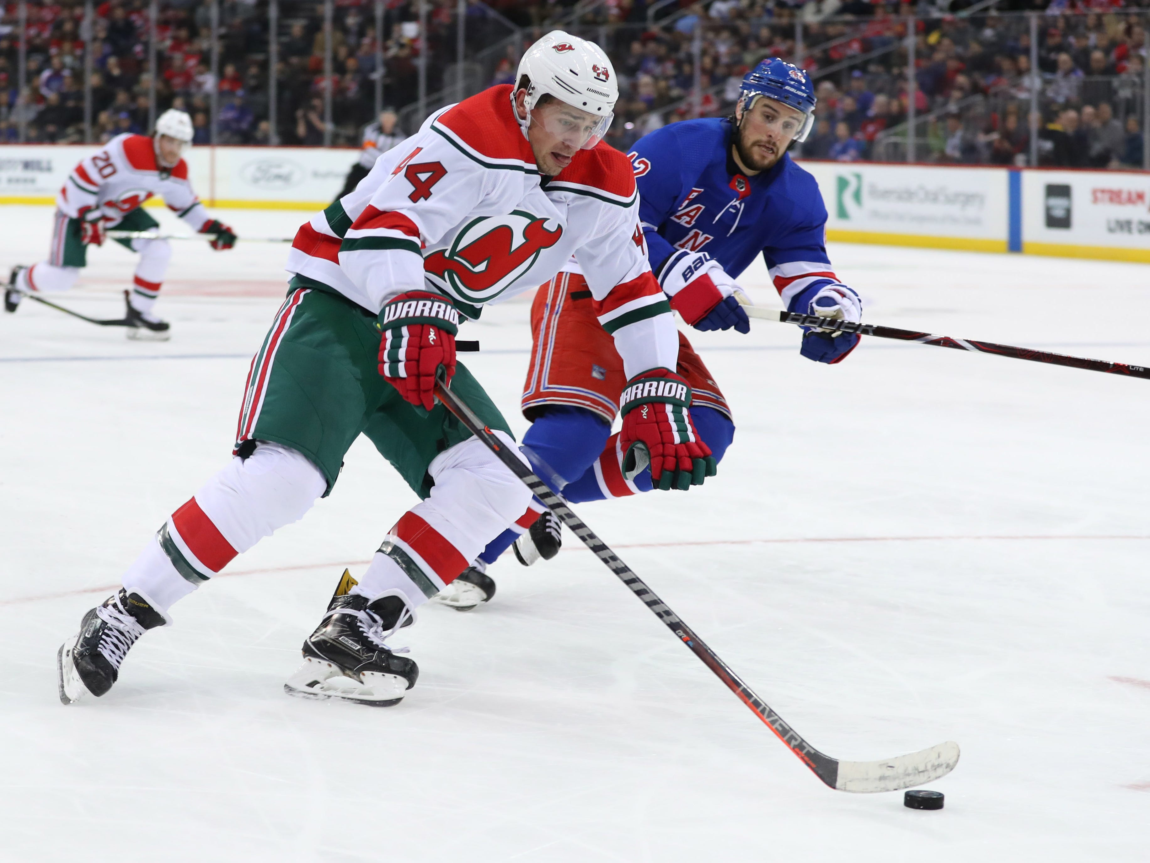 Jan 31, 2019; Newark, NJ, USA; New Jersey Devils left wing Miles Wood (44) skates with the puck while being defended by New York Rangers defenseman Brendan Smith (42) during the second period at Prudential Center.