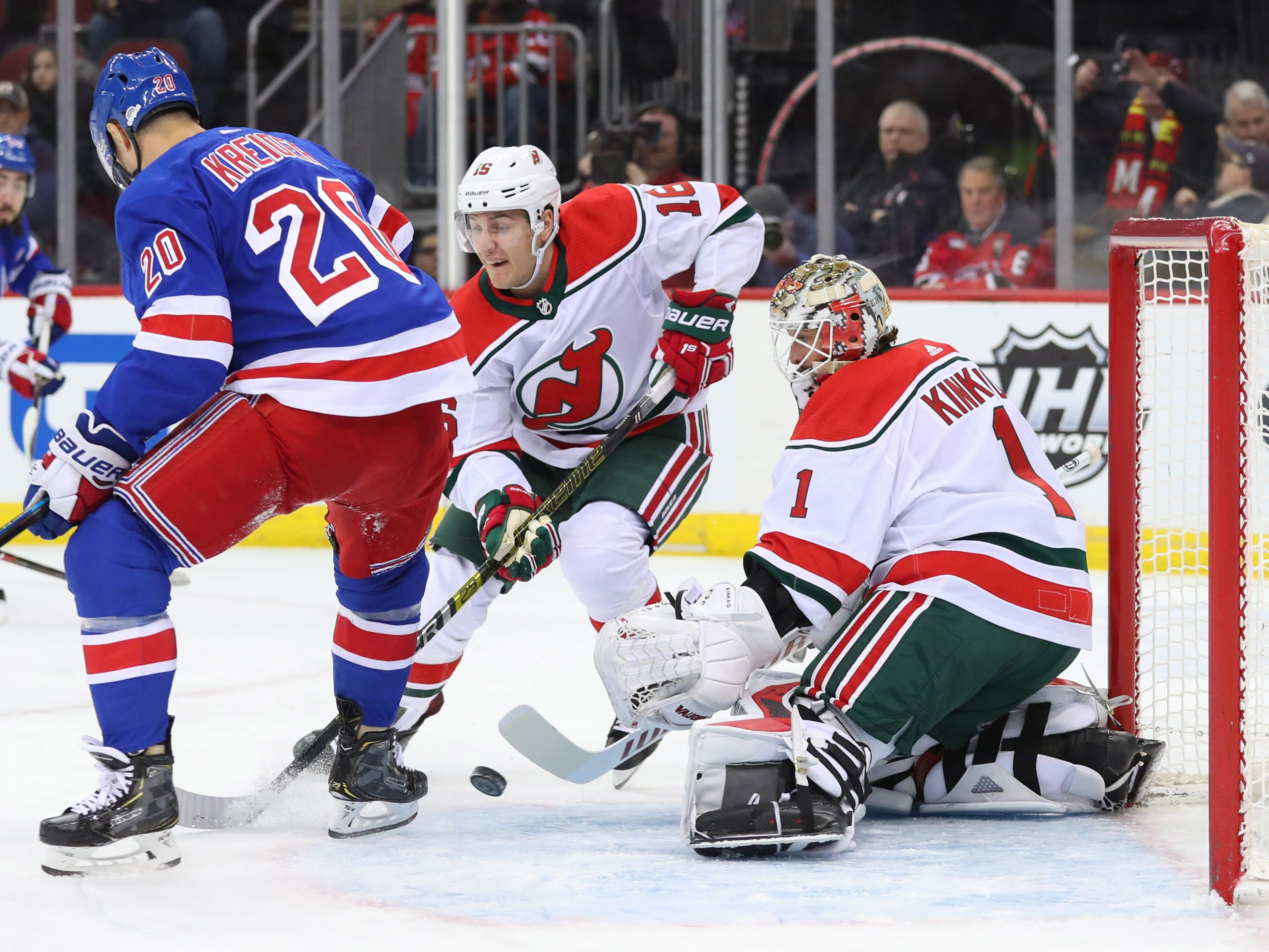 Jan 31, 2019; Newark, NJ, USA; New Jersey Devils goaltender Keith Kinkaid (1) makes a save while New York Rangers left wing Chris Kreider (20) and New Jersey Devils defenseman Steven Santini (16) battle for the loose puck during the first period at Prudential Center.