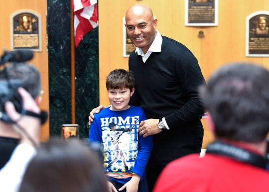 Baseball fan Ben Luck, of Connecticut, poses for a photo with Baseball Hall of Fame inductee Mariano Rivera during a news conference after Rivera's orientation tour of the National Baseball Hall of Fame and Museum, Friday, Feb. 1, 2019, in Cooperstown, N.Y. The former New York Yankees closer will be inducted on July 21. (AP Photo/Hans Pennink)