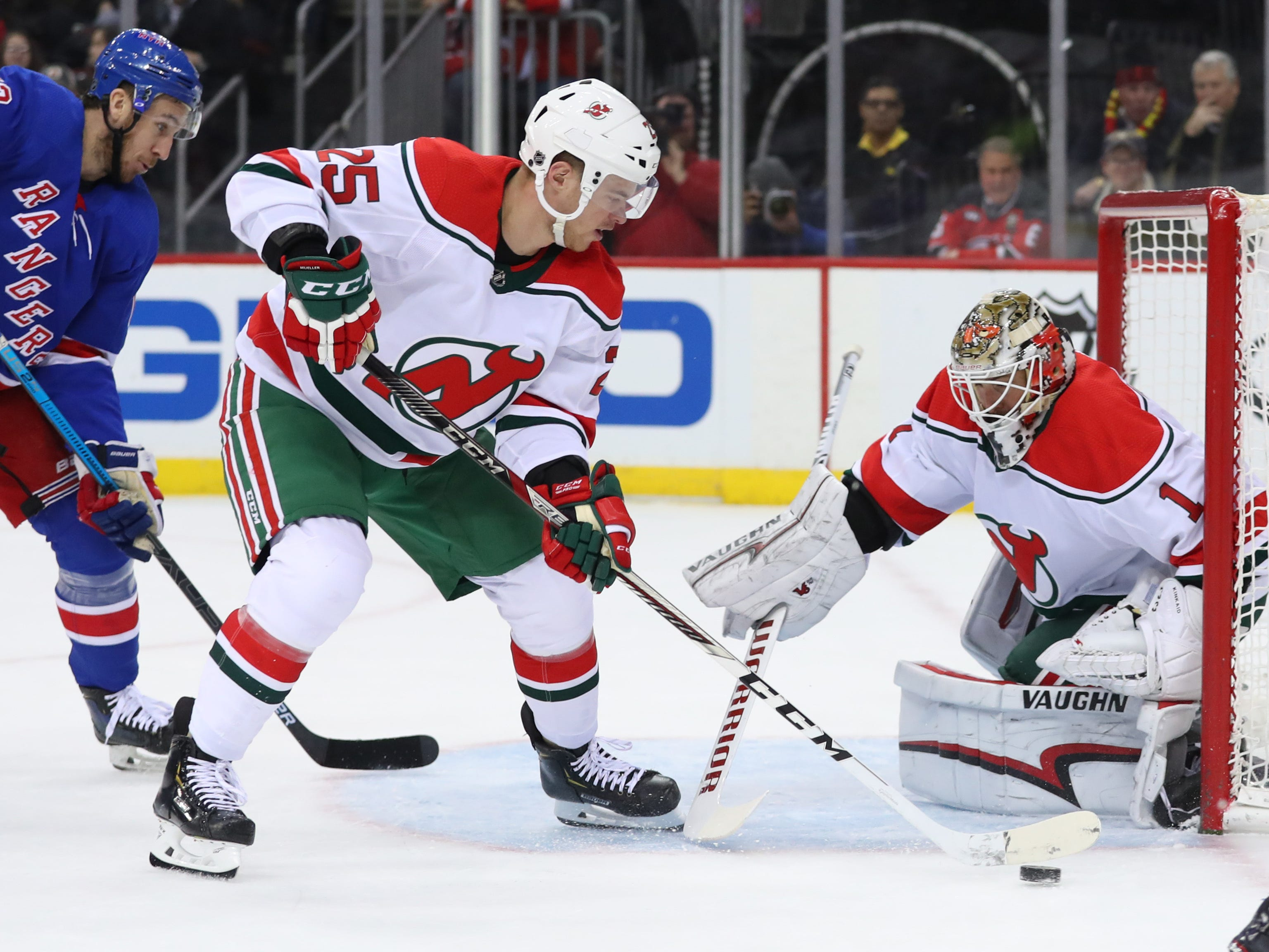 Jan 31, 2019; Newark, NJ, USA; New Jersey Devils defenseman Mirco Mueller (25) plays the puck in front of New Jersey Devils goaltender Keith Kinkaid (1) during the first period of their game against the New York Rangers at Prudential Center.