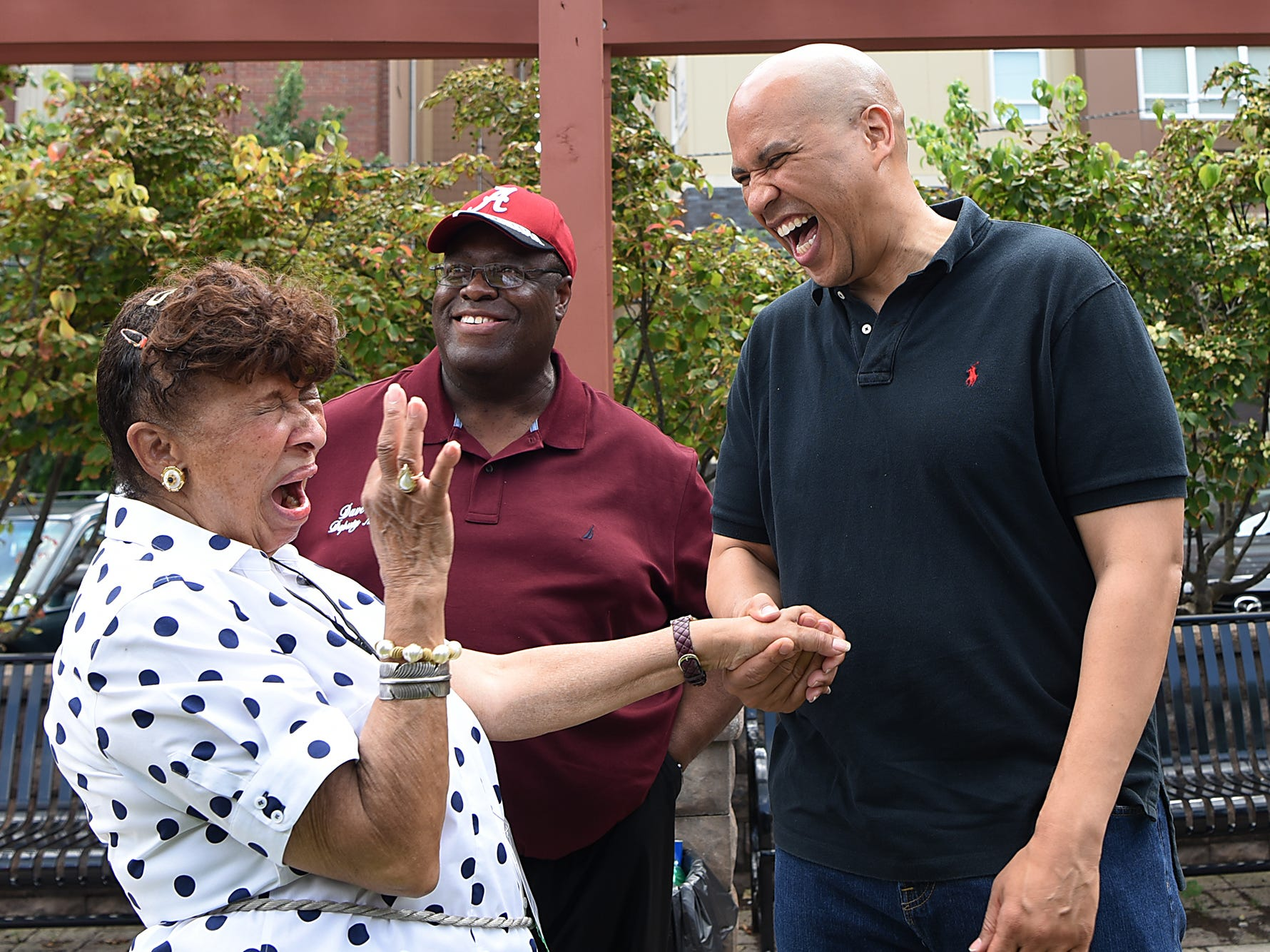 Lee Porter (left) and Senator Cory Booker (right) share a laugh along with Dave Sims. Fair Housing Council of Northern New Jersey holds a picnic in Hackensack on Friday August 10, 2018.