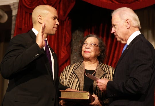 Cory Booker stands with his mother Carolyn in the Old Senate Chamber as he is sworn into the Senate by Vice-President Joe Biden in October 2013.