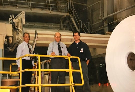 At their Number 11 paper machine, Marcal Chairman Robert Marcalus is flanked by son Peter Marcalus and grandson Michael Bonin with a freshly made jumbo roll of tissue, pictured in 2002.