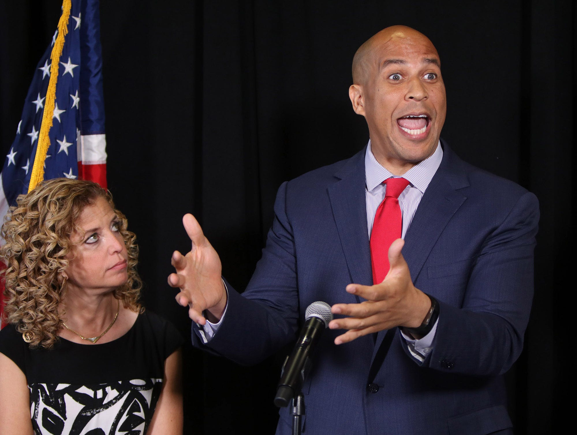 DNC Chairwoman Debbie Wasserman Schultz watches as US Senator Cory Booker (D-NJ) speaks during a press conference to denounce the divisive rhetoric surrounding Donald Trump's Republican convention. Senator Al Franken (D-MN) also appeared at event that was held at a law office in Cleveland, OH, Thursday July 21, 2016.