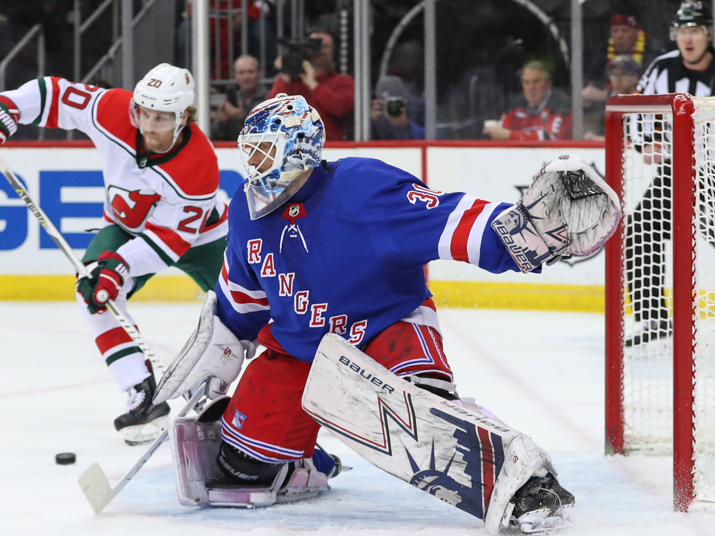 Jan 31, 2019; Newark, NJ, USA; New Jersey Devils center Blake Coleman (20) plays the puck while New York Rangers goaltender Henrik Lundqvist (30) defends his net during the second period at Prudential Center.