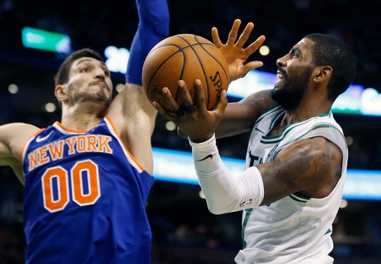 Boston Celtics' Kyrie Irving, right, goes up to shoot against New York Knicks' Enes Kanter (00) during the fourth quarter of an NBA basketball game in Boston, Tuesday, Oct. 24, 2017. The Celtics won 110-89. (AP Photo/Michael Dwyer)