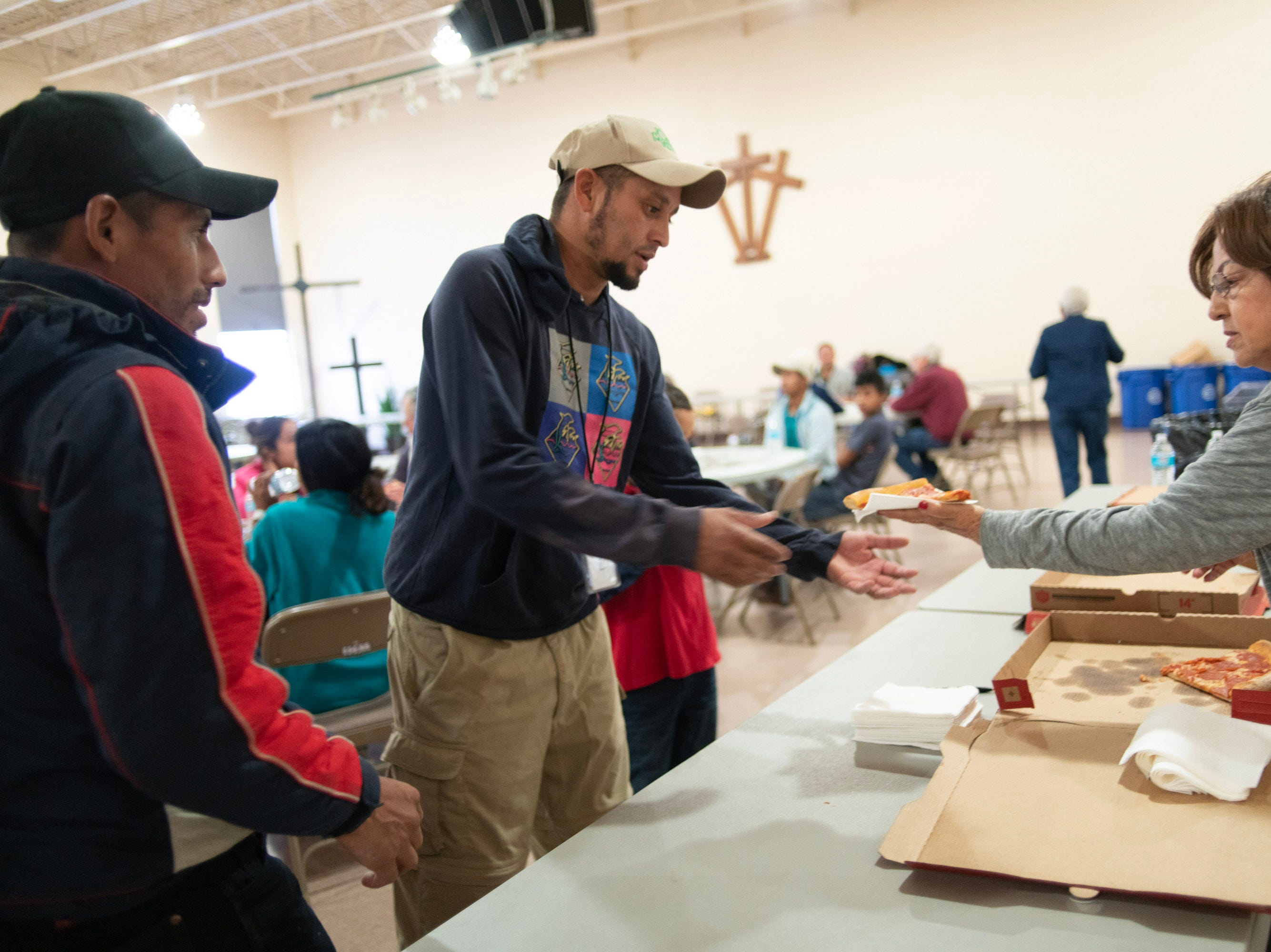 A volunteer at a migrant shelter in Doña Ana County serves pizza to immigrants just arriving from ICE detention.
