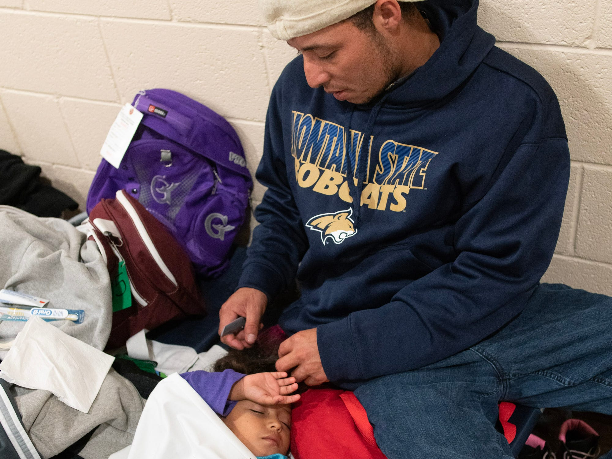 Eduwin Nisama combs his 3-year-old daughter Adriana's hair while she sleeps at a migrant shelter in Doña Ana County.