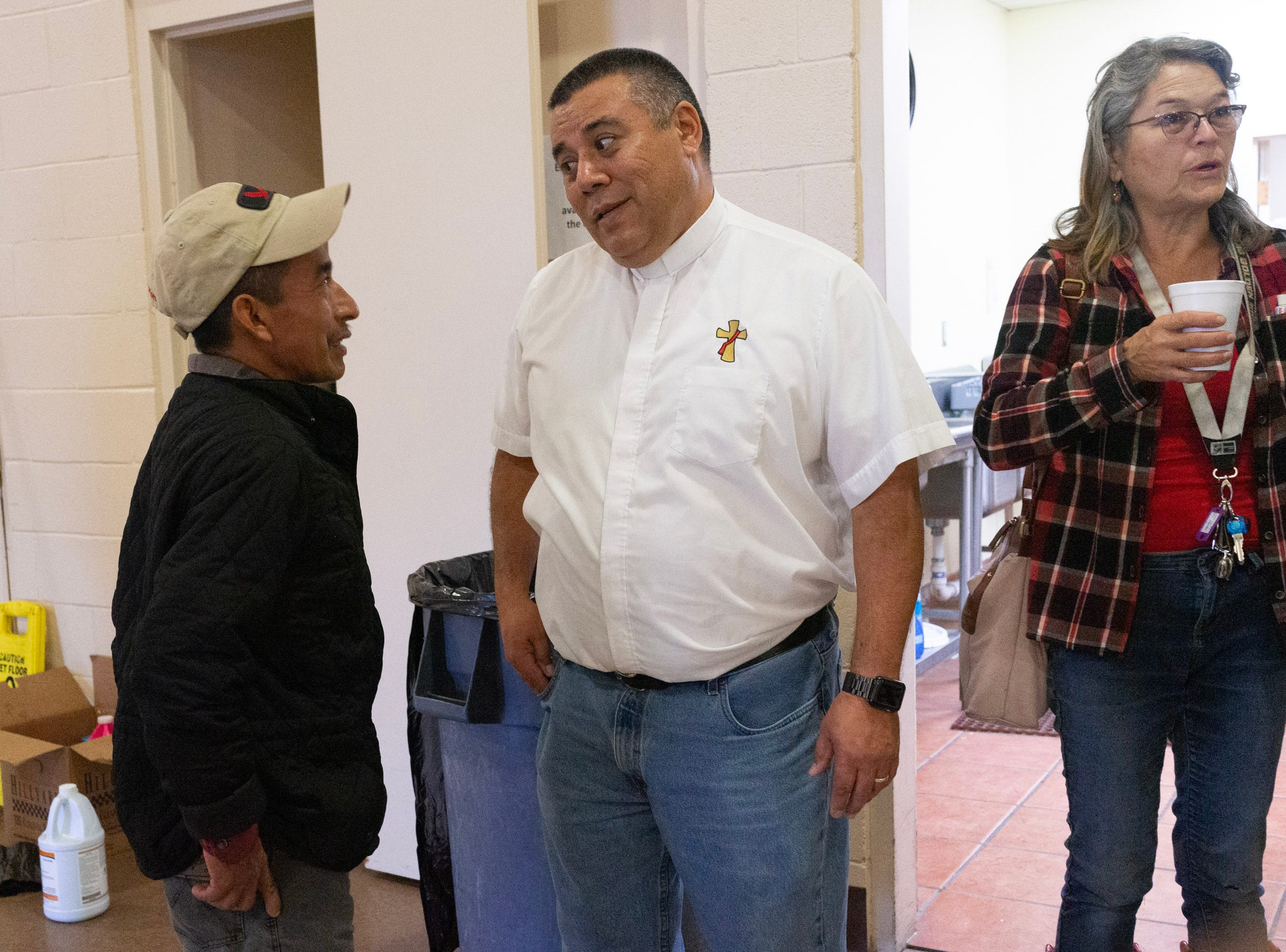 Deacon Lonnie Briseño talks with immigrant Pedro Salas Cardona.