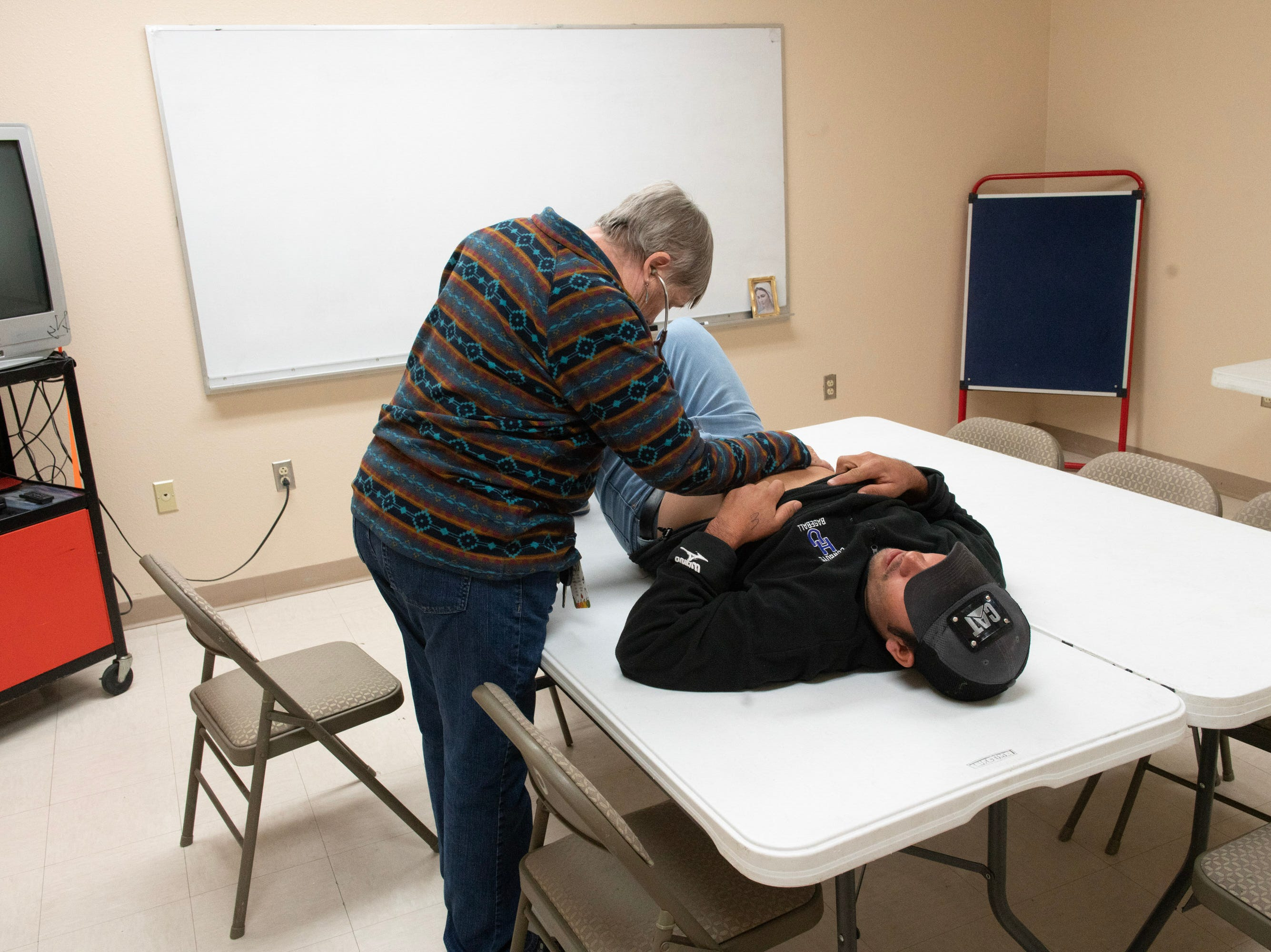 A volunteer doctor at a shelter in Doña Ana County examines an immigrant man complaining of acute abdominal pain.