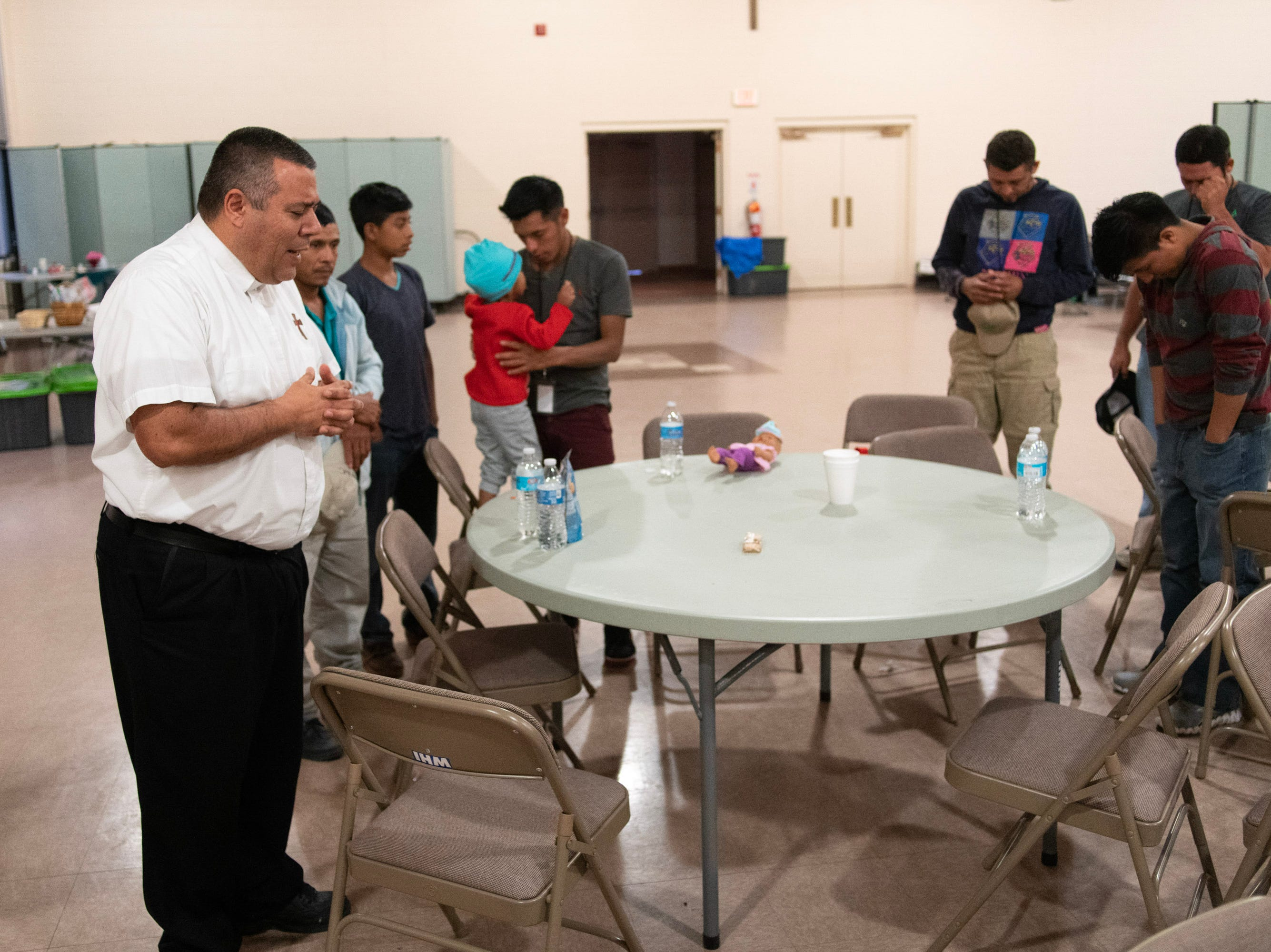Deacon Lonnie Briseño and immigrants pray for safe journeys when they leave a Doña Ana County shelter.