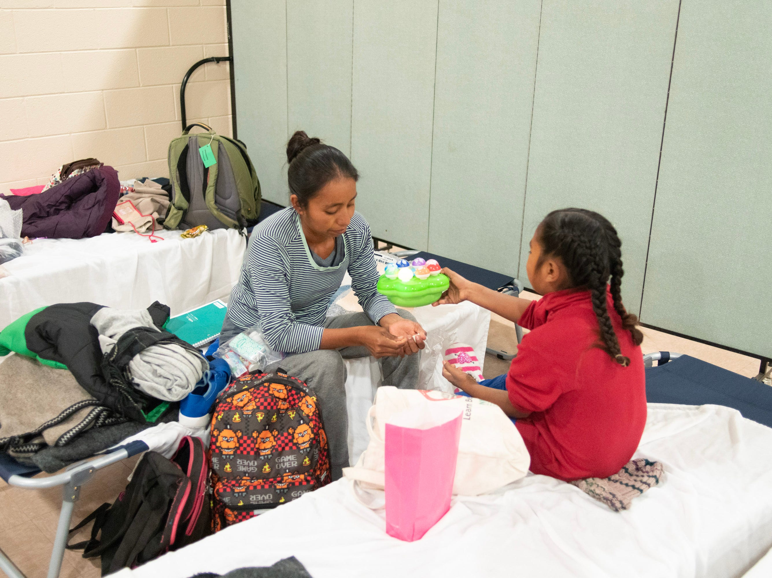 Marcela Teyuco and her daughter play games before getting ready for bed at a migrant shelter in Doña Ana County.