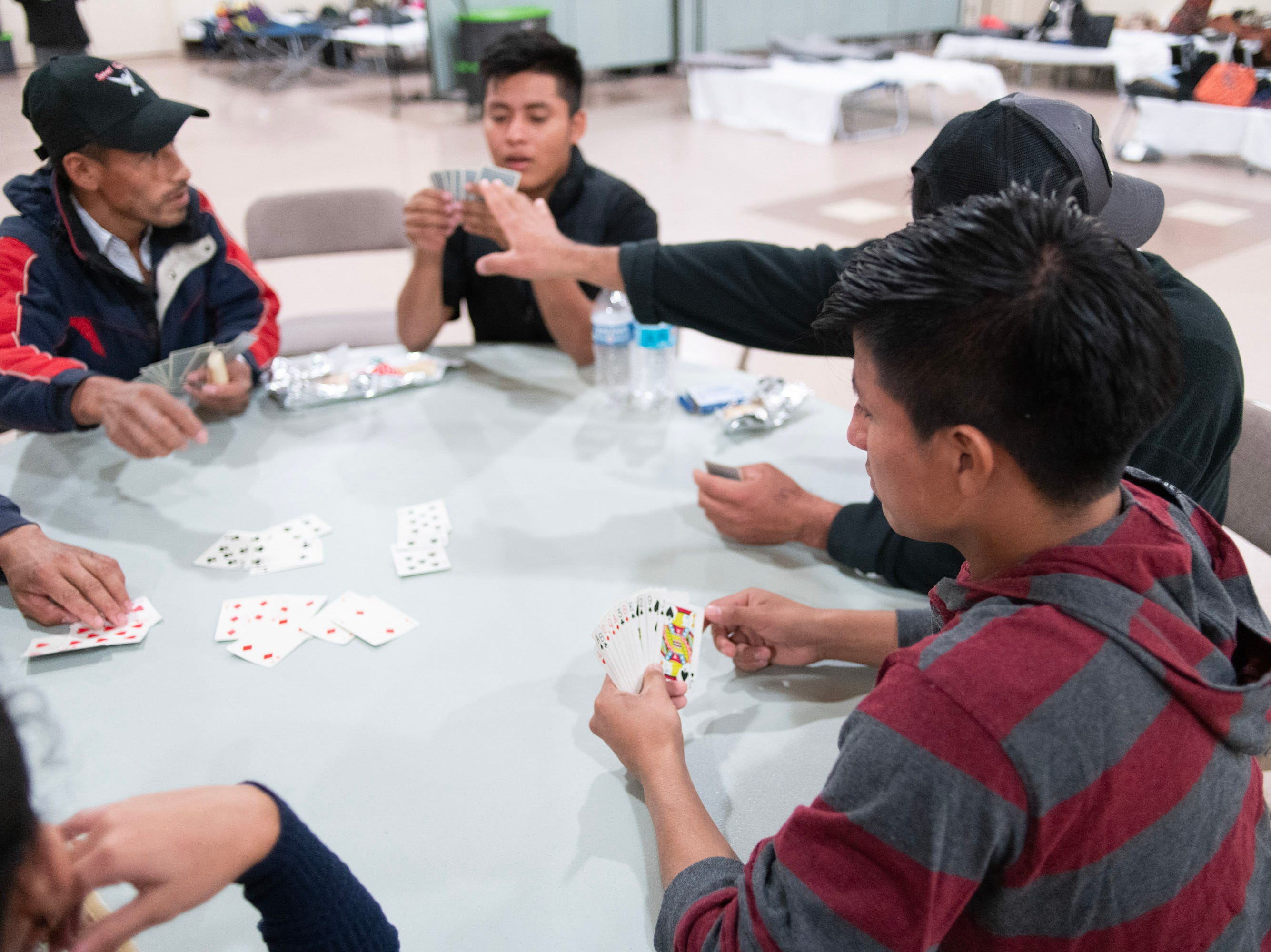 Migrants at a Doña Ana County shelter play cards to pass the time before dinner.