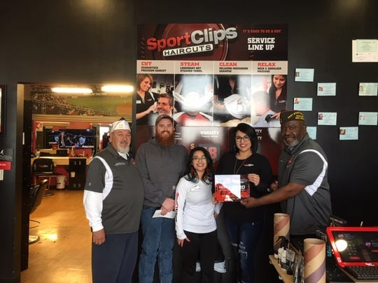 VFW members presenting an appreciation plaque to Sport Clips of Las Cruces for their support of the Help A Hero Scholarship Program. From right to left, District Commander Cano, Mark Allen, scholarship recipient, Alyssa Rodriguez, assistant manager, Meagan Guerra, manager, and Past State Commander Hampton.