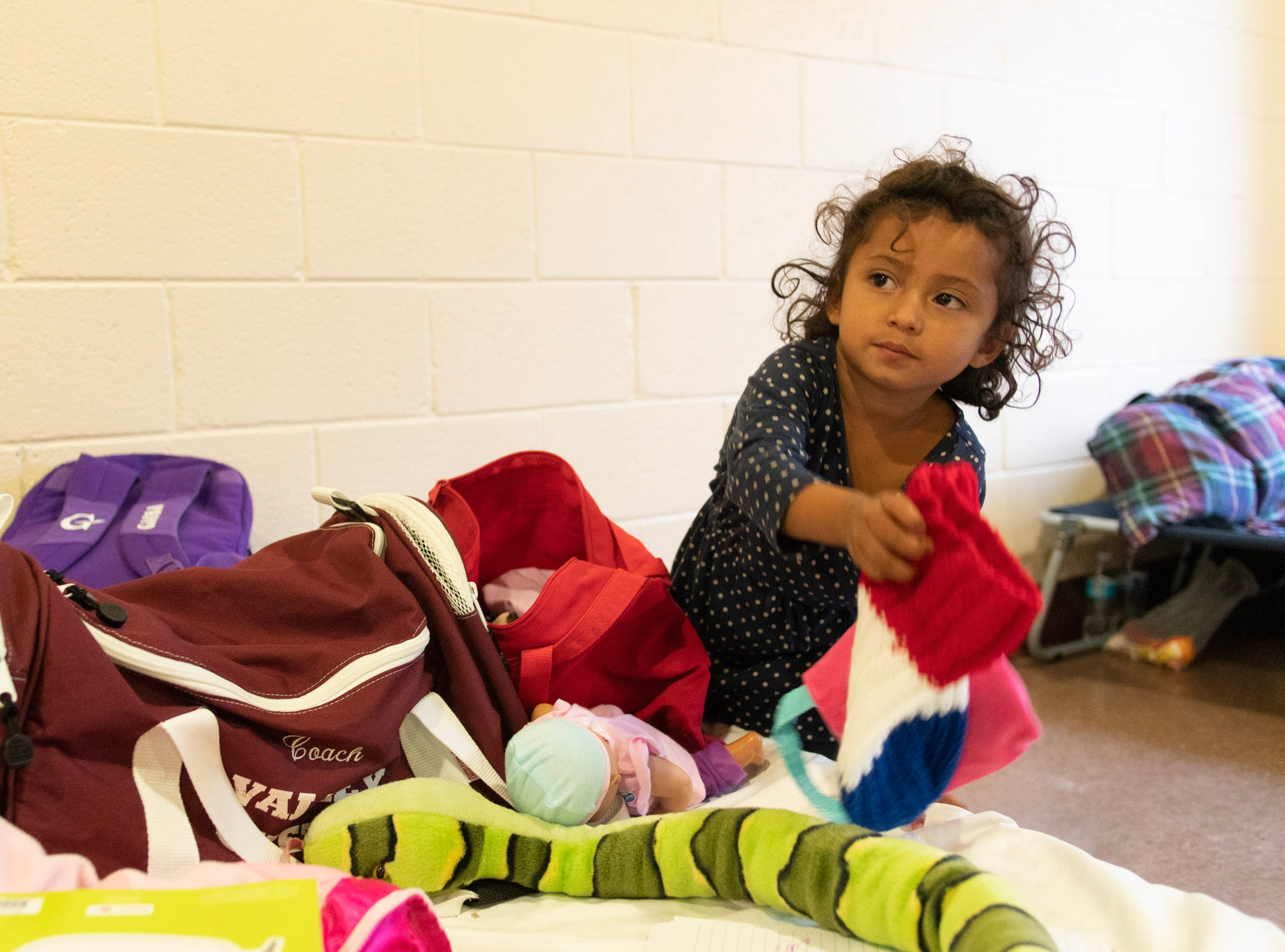 """For children who migrate north, """"the risks are enormous,"""" says Marlene Baska, who runs a medical clinic in Animas, New Mexico. """"With their developmental status, the trauma of the experience will affect the rest of their lives."""" Pictured is Adriana, age 3, sorting through her new belongings, donated at the Immaculate Heart of Mary church."""