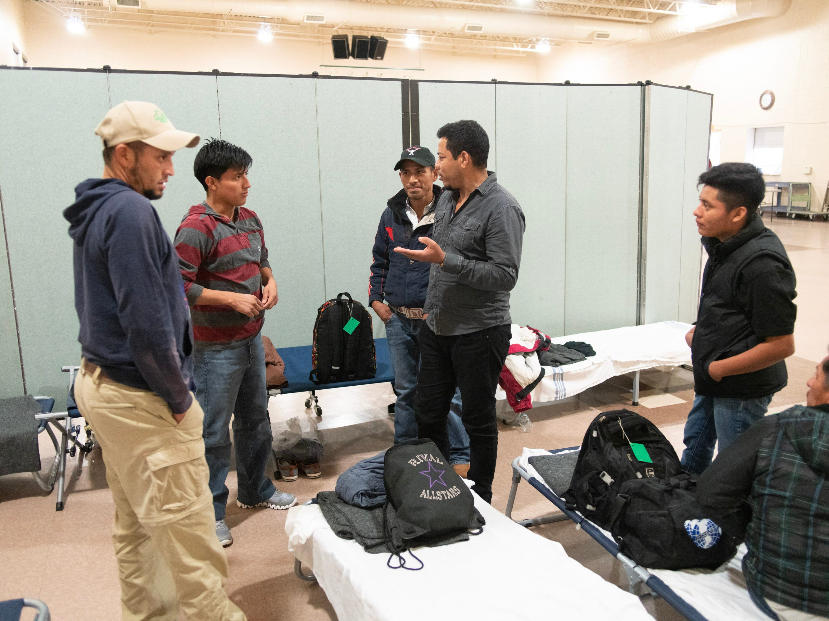 Men gather on the men's side of a migrant shelter in Doña Ana County to chat about their journeys and their destinations.