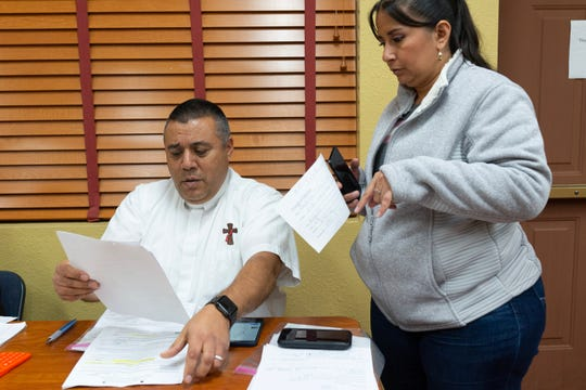 Deacon Lonnie Briseño, left, organizes paperwork for Project Oak Tree.
