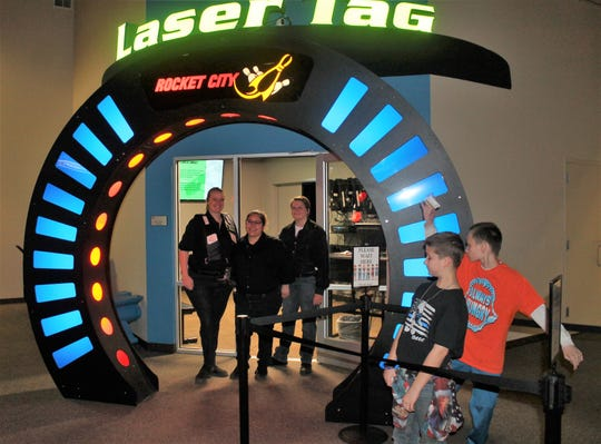 Rocket City Fun Center workers Mindy Gonzalez, Morgan Hemish and Mary Cobb along with two children waiting to get in stand in front of the Laser Tag Arena at the Rocket City Fun Center.