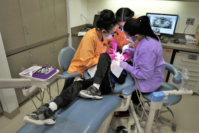 Eight-year-old Zaiden Valdez has his teeth worked on by San Juan College students Arely Tarango, left, Brooke Ramirez, center, and Valeria Maldonado during the college's 2019 Give Kids a Smile Day clinic.