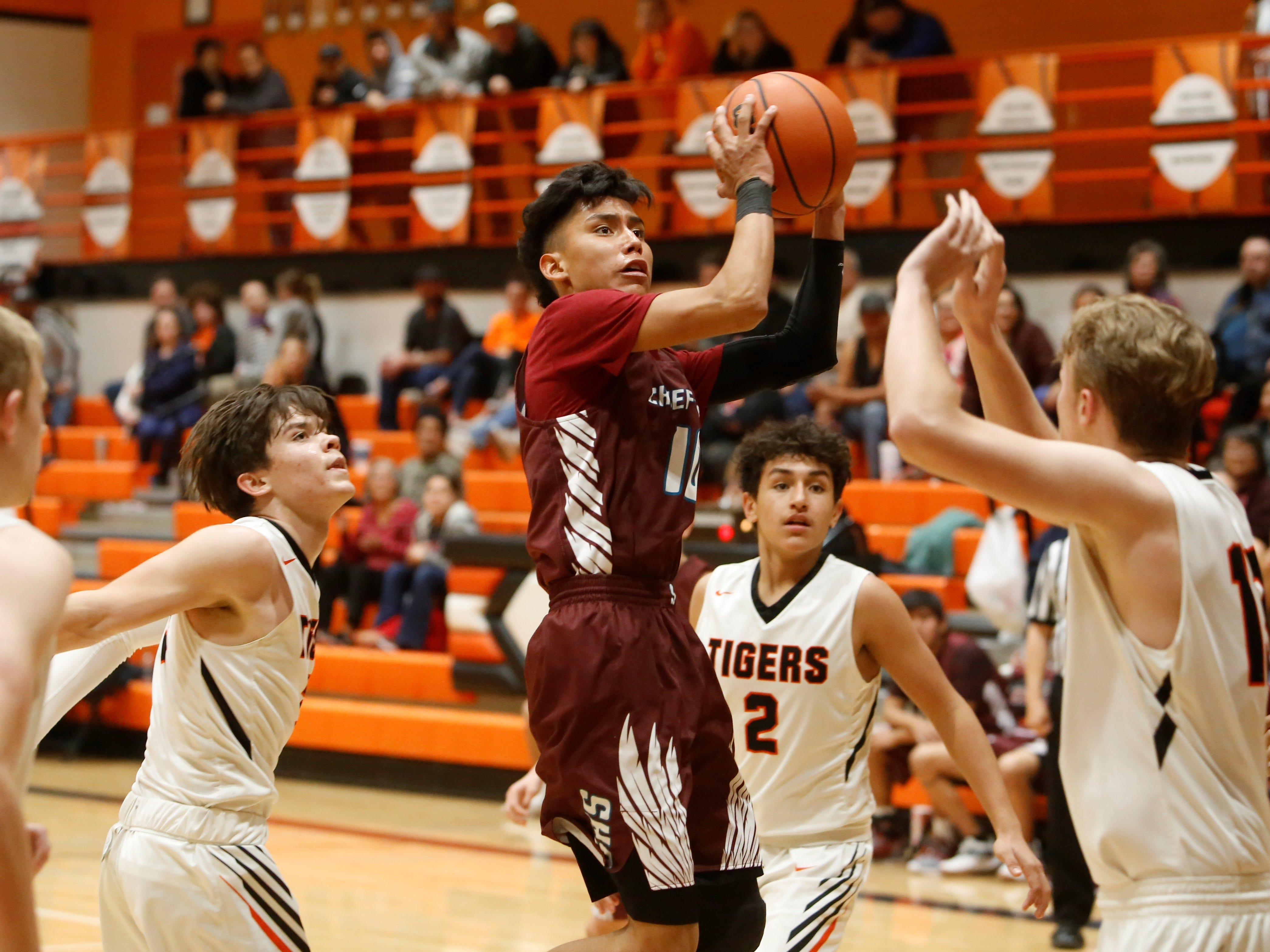 Shiprock's Trevor Etcitty shoots and makes a contested basket against Aztec during Thursday's District 1-4A game at Lillywhite Gym in Aztec.