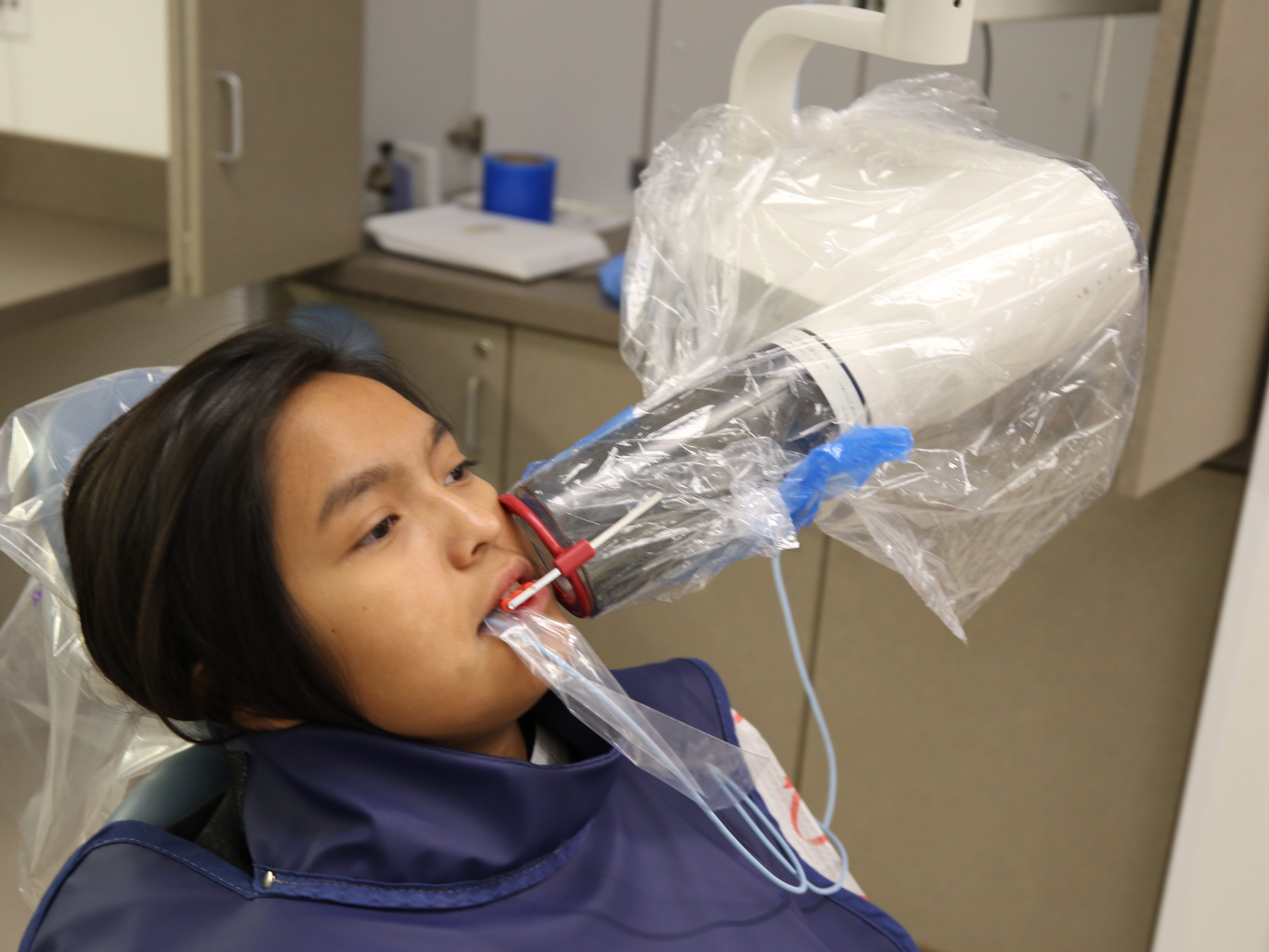 Twelve-year-old Fabianna Scott's prepares for an x-ray examination Friday morning at San Juan College's Give Kids a Smile Event. There were about 33 juveniles scheduled for the free dental clinic.