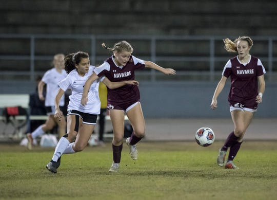 Kayla Fernandez (11) and Autumn Slaybaugh (15) go after a loose ball during the District 1-4A girls soccer tournament final between Niceville and Navarre at Navarre High School on Thursday, January 31, 2019.  Niceville won 7-6 in penalty kicks.