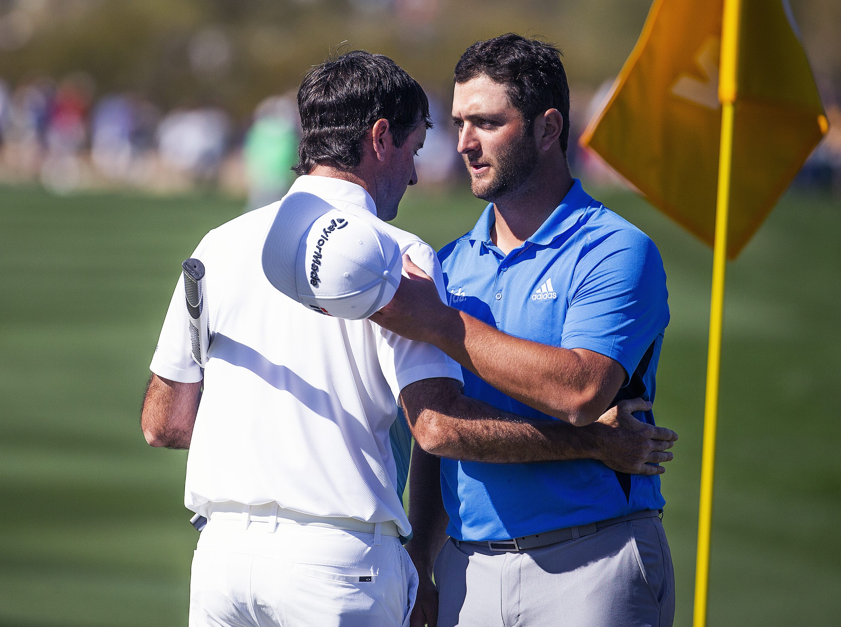 Bubba Watson, left, and Jon Rahm embrace at the end of their round on the 9th hole during the second round of the Waste Management Phoenix Open at the TPC Scottsdale, Friday, February 1, 2019.  After Watson putted and finished his round he was in second place at 9 under par.