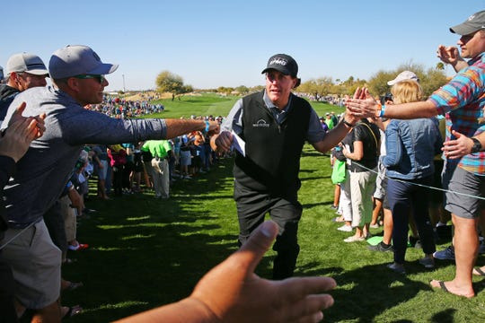 Phil Mickelson receives high-fives from his fans after finishing his second round on Feb. 1 during the Waste Management Phoenix Open at the TPC Scottsdale Stadium Course.