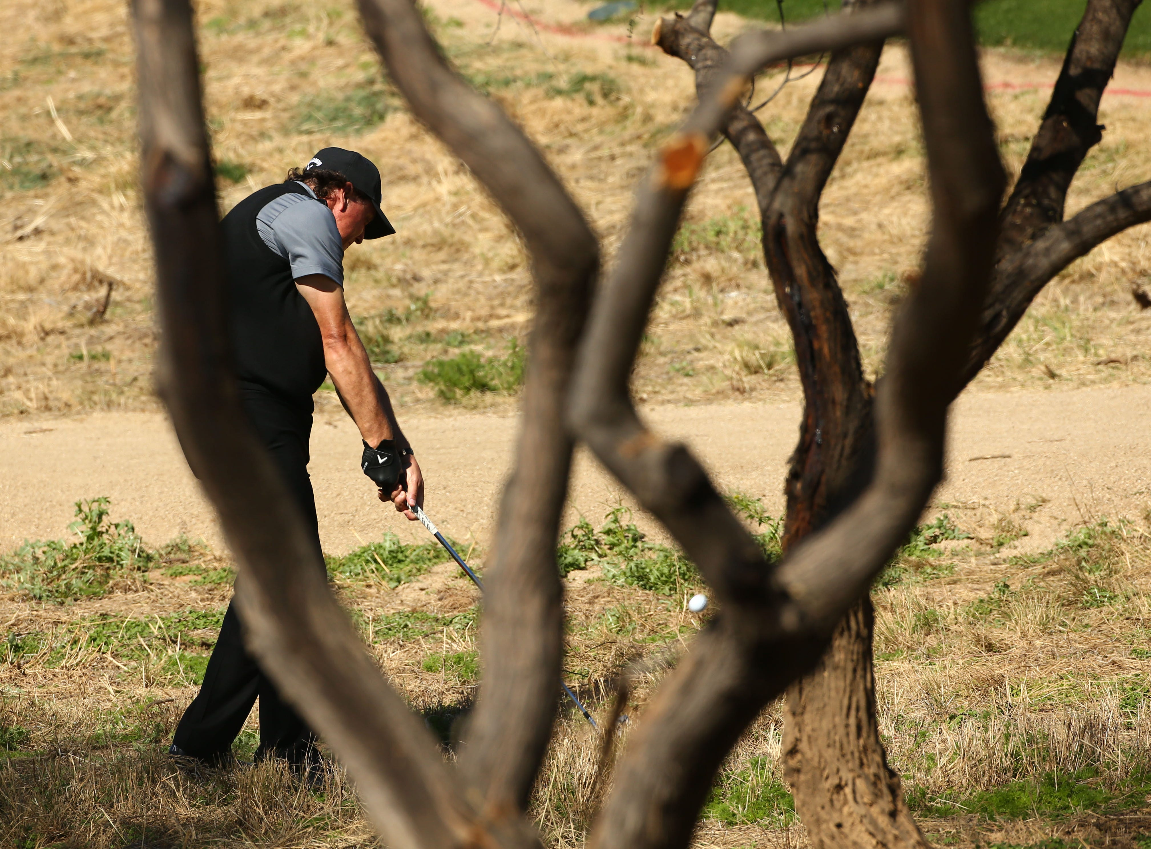 Phil Mickelson plays his second shot over trees in a desert area on the 9th hole during second round action on Feb. 1 during the Waste Management Phoenix Open at the TPC Scottsdale Stadium Course.