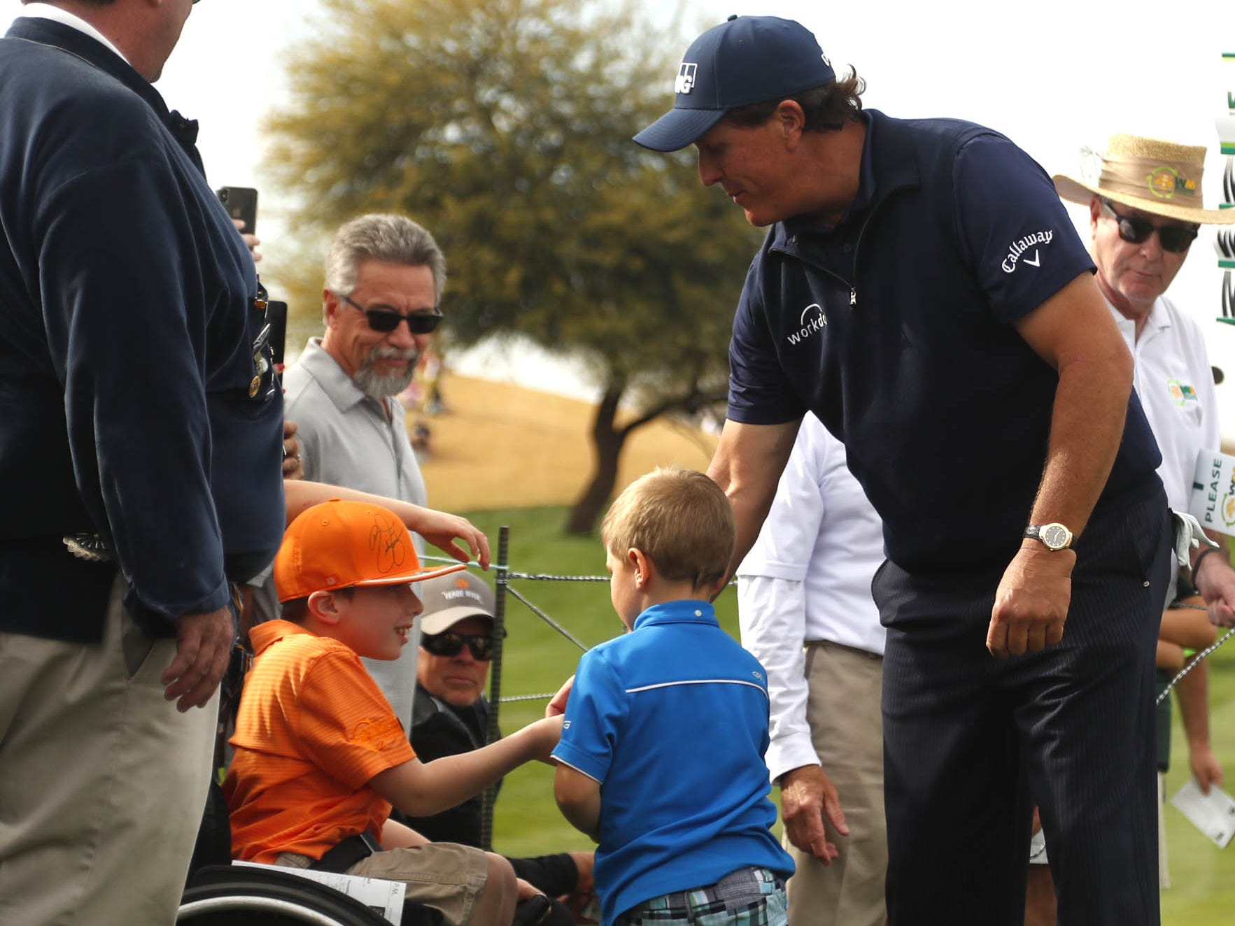 Phil Mickelson shakes a hand of a young fan after making a birdie on the 9th hole during first round of the Waste Management Phoenix Open at TPC Scottsdale in Scottsdale, Ariz. on January 31, 2019.