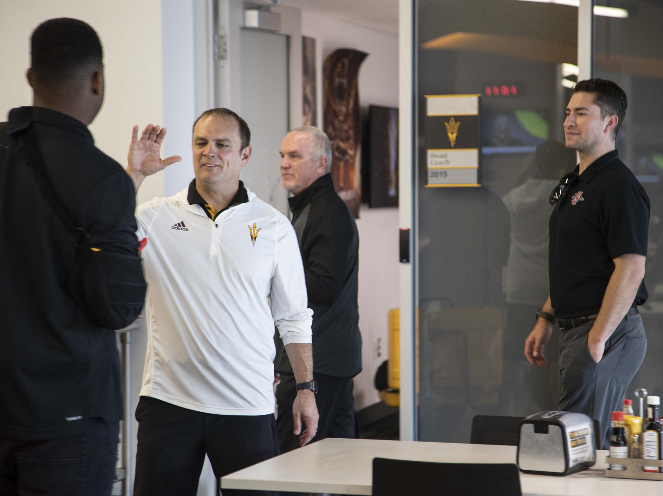 Defensive coordinator Danny Gonzales gives hi five to players during the ASU Spring Football media day at ASU Tempe campus.