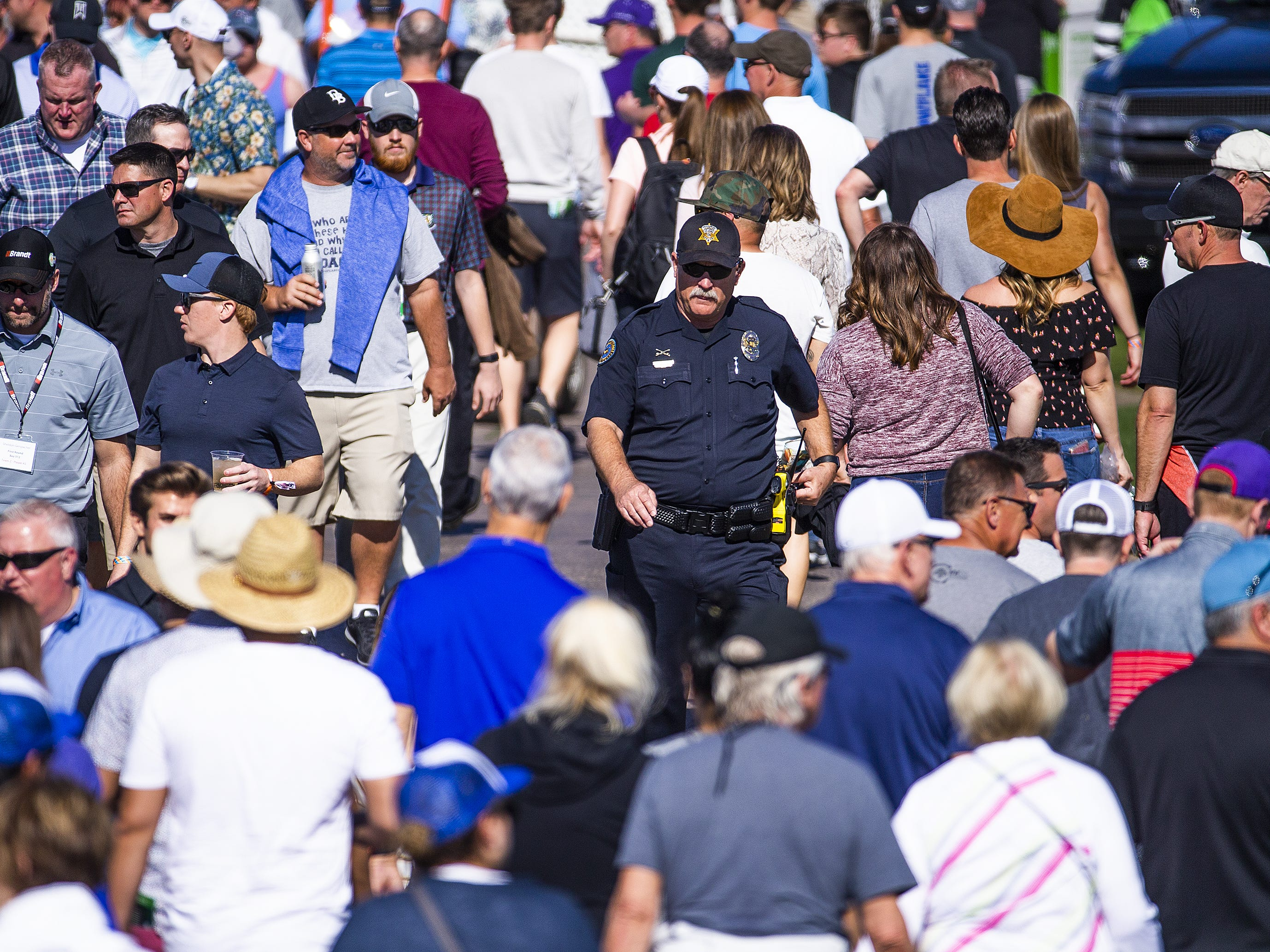 A police officer makes his way through the crowd during the second round of the Waste Management Phoenix Open at the TPC Scottsdale, Friday, February 1, 2019.