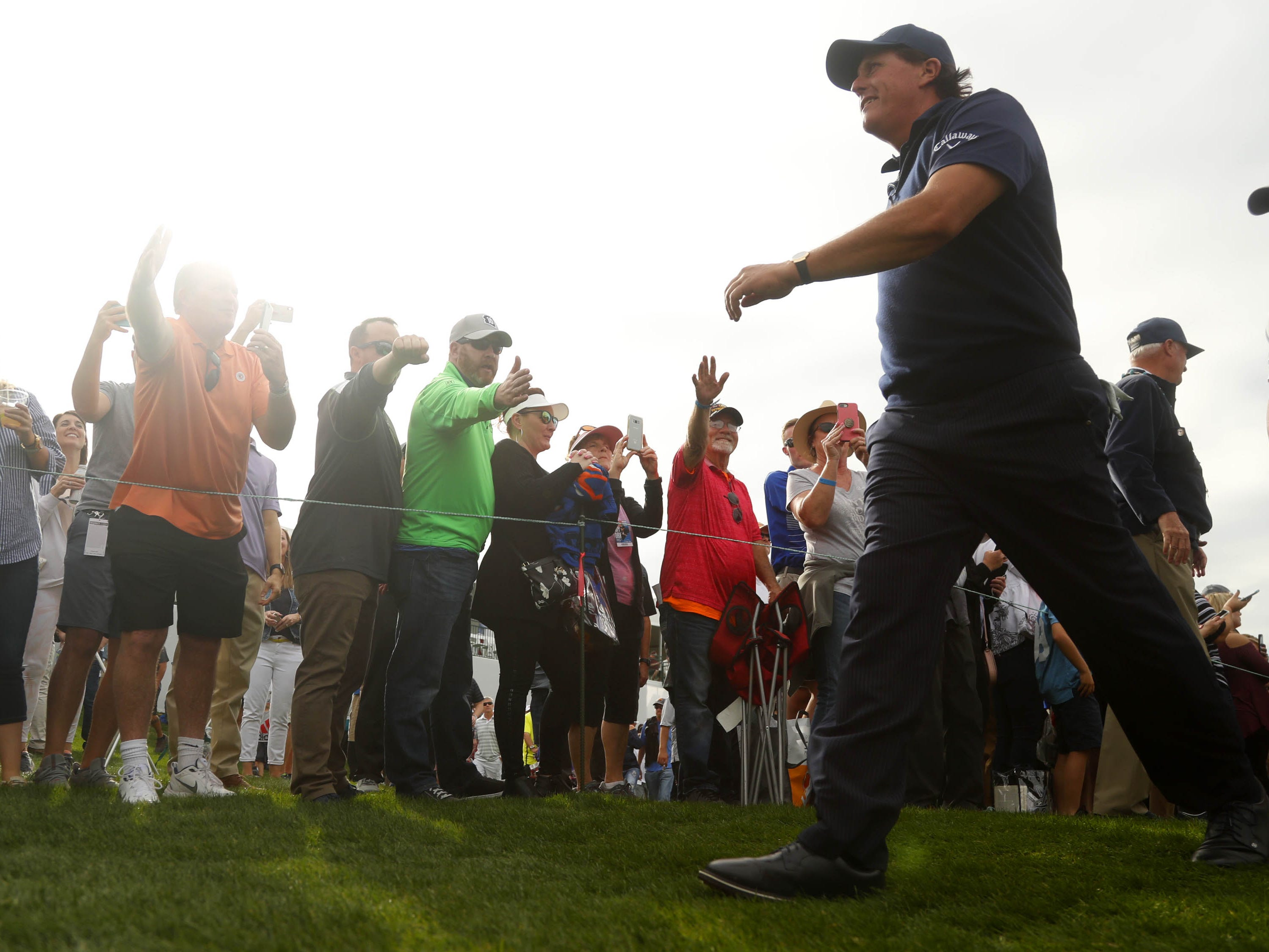 Phil Mickelson walks off the 9th hole greeted by fans during first round of the Waste Management Phoenix Open at TPC Scottsdale in Scottsdale, Ariz. on January 31, 2019.