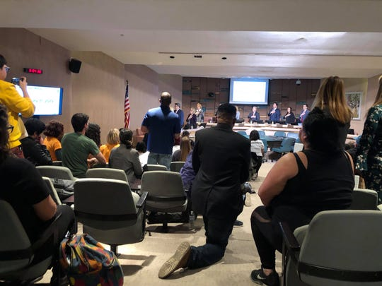 Protesters kneel during the Tempe City Council meeting on Jan. 31, 2019, in protest of the fatal police shooting of 14-year-old Antonio Arce.