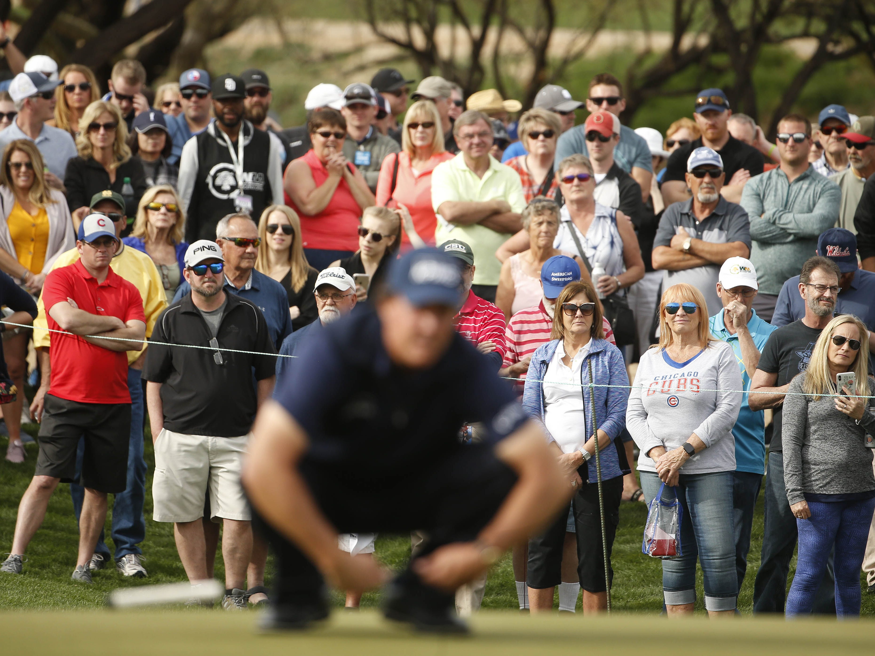 Fans watch Phil Mickelson line up a putt on the 9th green during first round of the Waste Management Phoenix Open at TPC Scottsdale in Scottsdale, Ariz. on January 31, 2019.