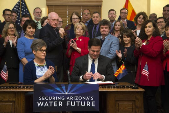 Gov. Doug Ducey (right) signs the Drought Contingency Plan on Jan. 31, 2019, in the historic Senate Chamber, at the Arizona state Capitol.