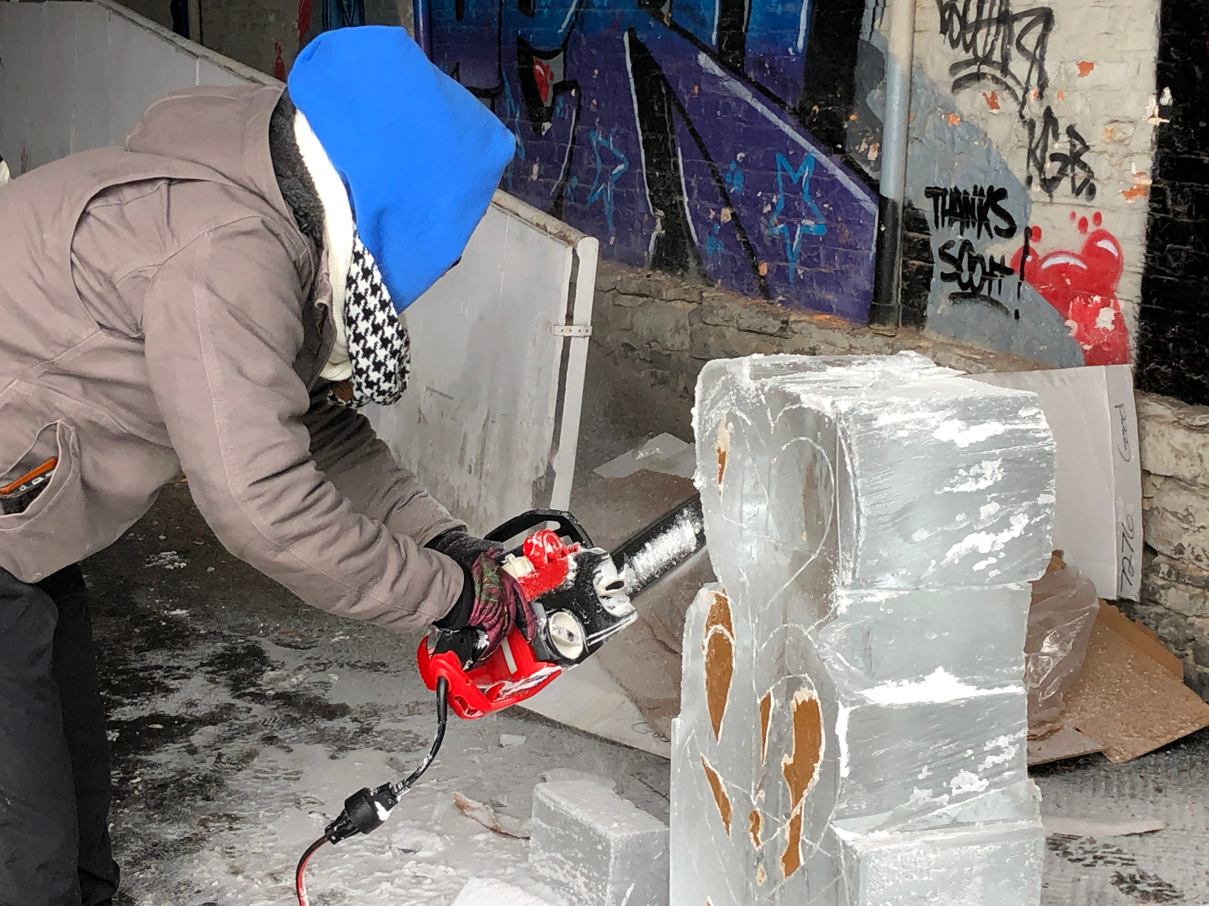 After a brief break to get warm inside the farmers market, Emily Schmidt was back to work shaping hearts in the ice with a chainsaw.