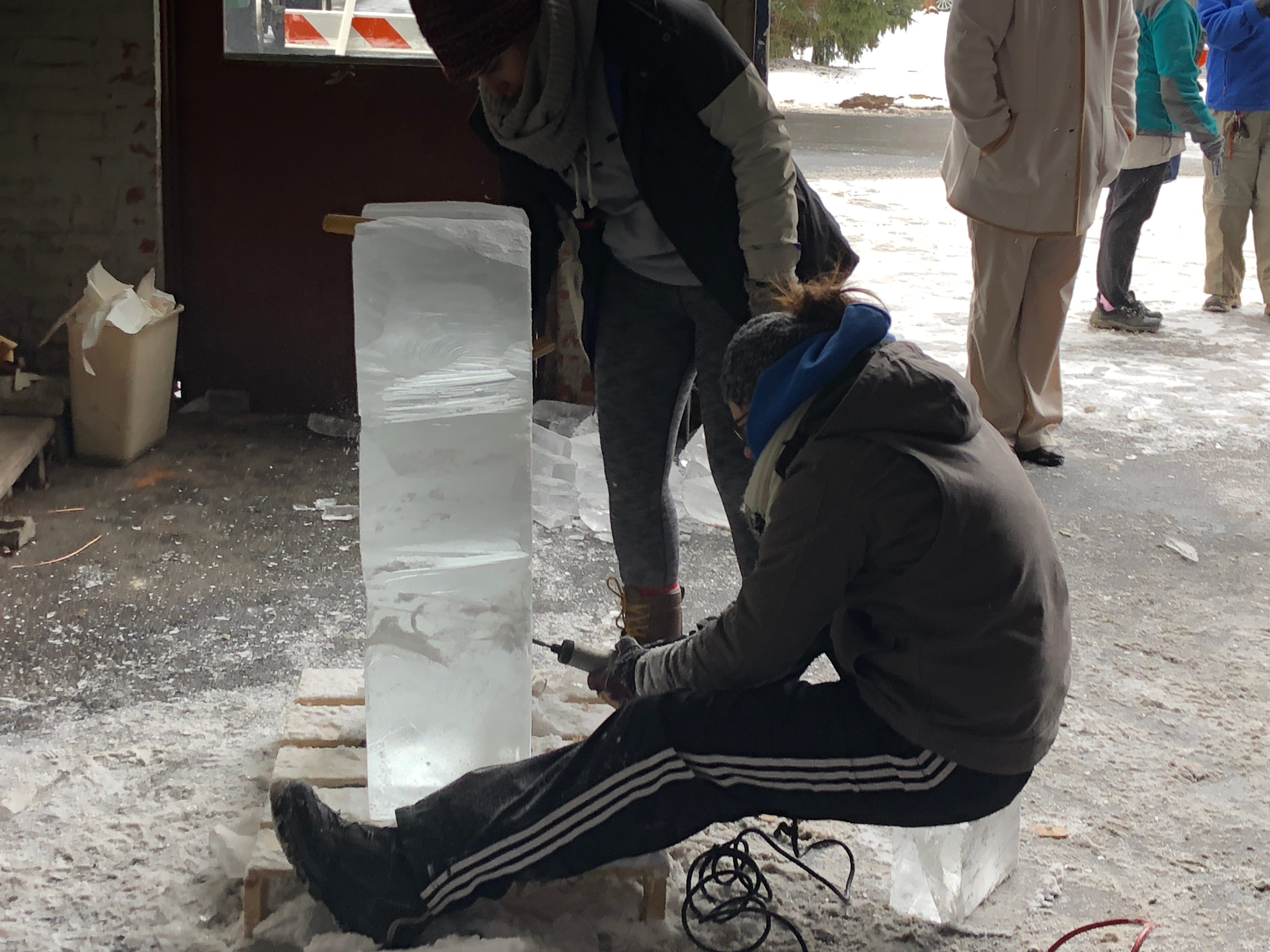 Whatever you have to do to get the job done. Emily Schmidt takes a seat on a hunk of idea to etch hearts into her sculpture.
