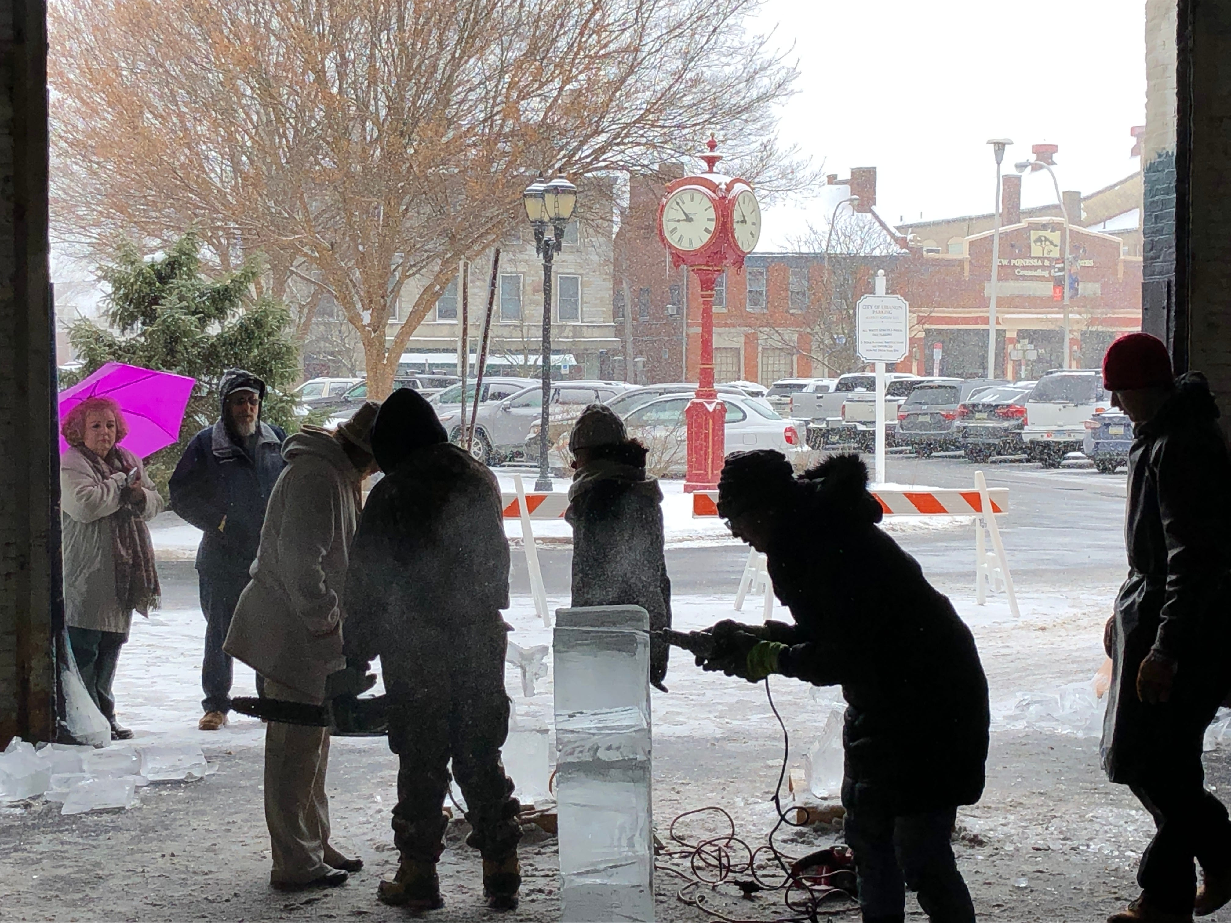 Snow continues to fall downtown as LCCTC students complete their ice sculptures.